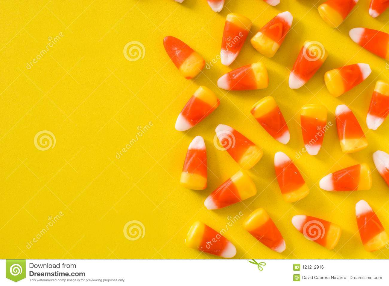 typical halloween candy corn on yellow background. stock photo