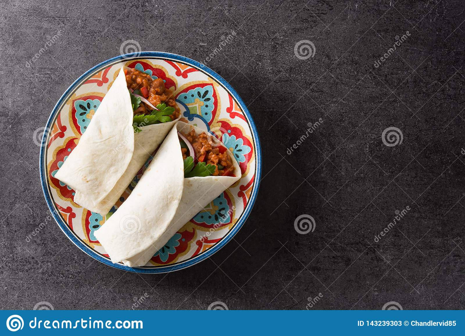 Typical Mexican burrito wrap with beef, frijoles and vegetables on black background.