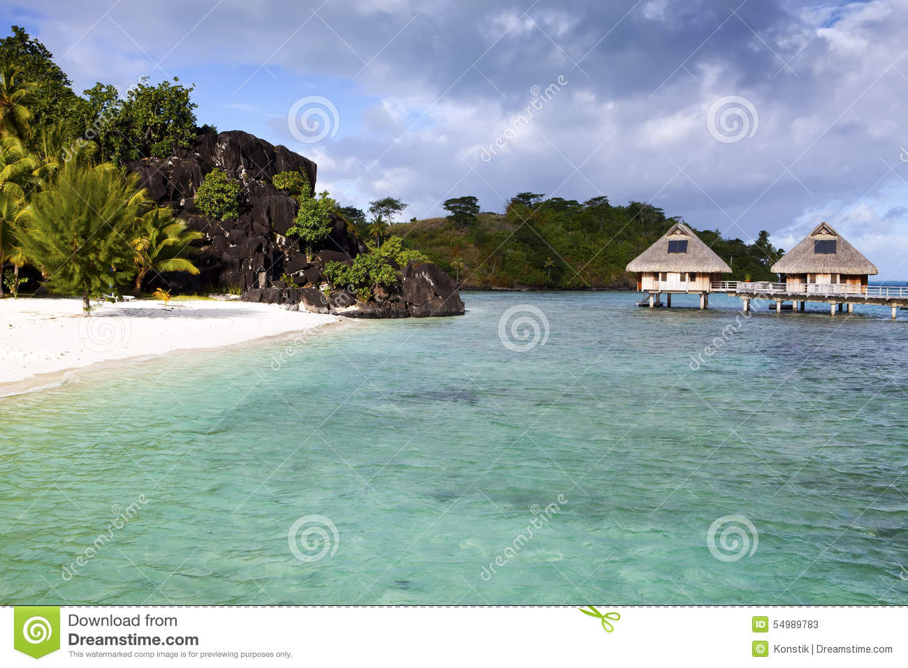 Typical Polynesian Landscape - Island With Palm Trees And Small Houses On  Water In The Ocean And Mountains On A Background Stock Photo - Image:  54989783