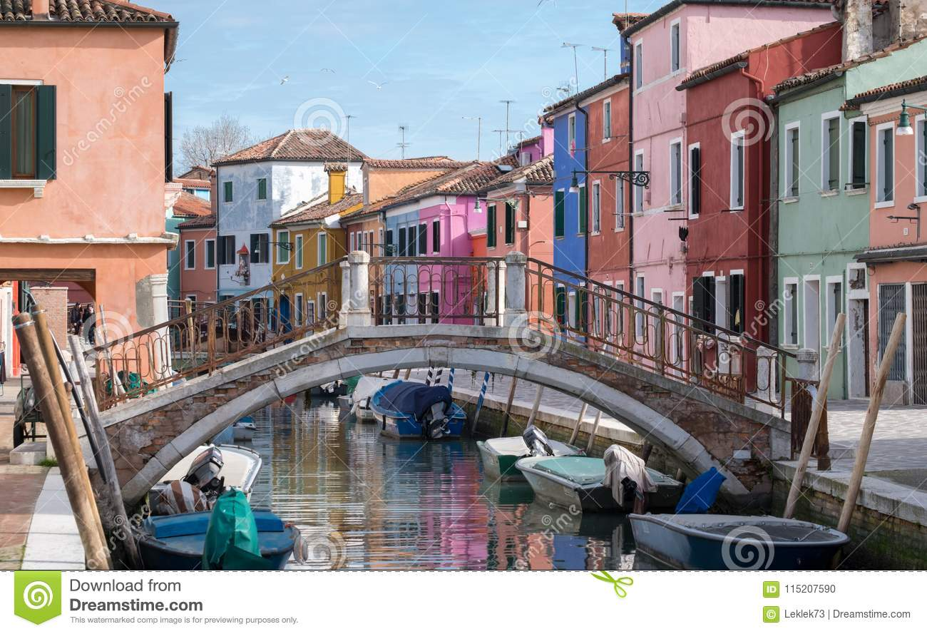 Typical street scene showing brighly painted houses and bridge over canal on the island of Burano, Venice.