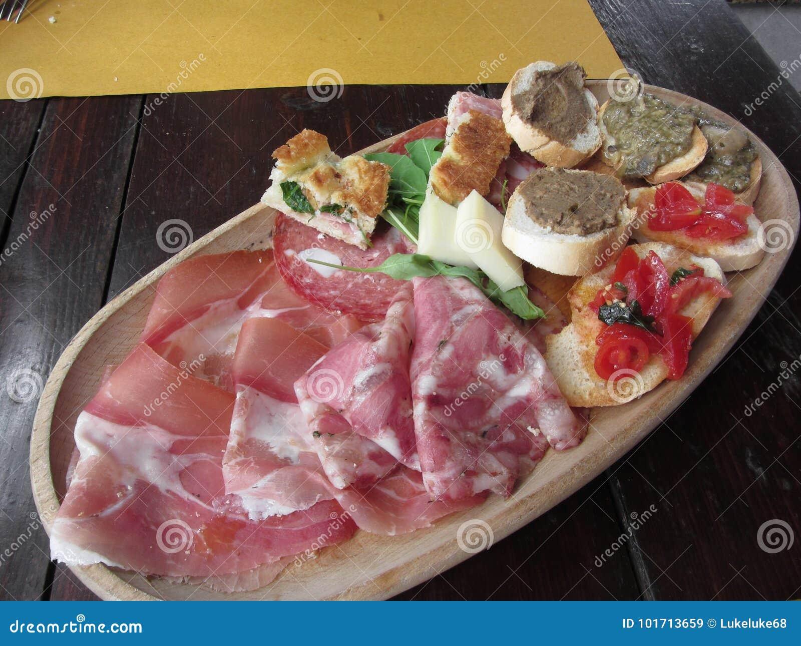 Typisch rustiek Toscaans voorgerecht met crostini, prosciutto, hoofdkaas, salami, kaas op een houten dienblad Italiaanse aanzet