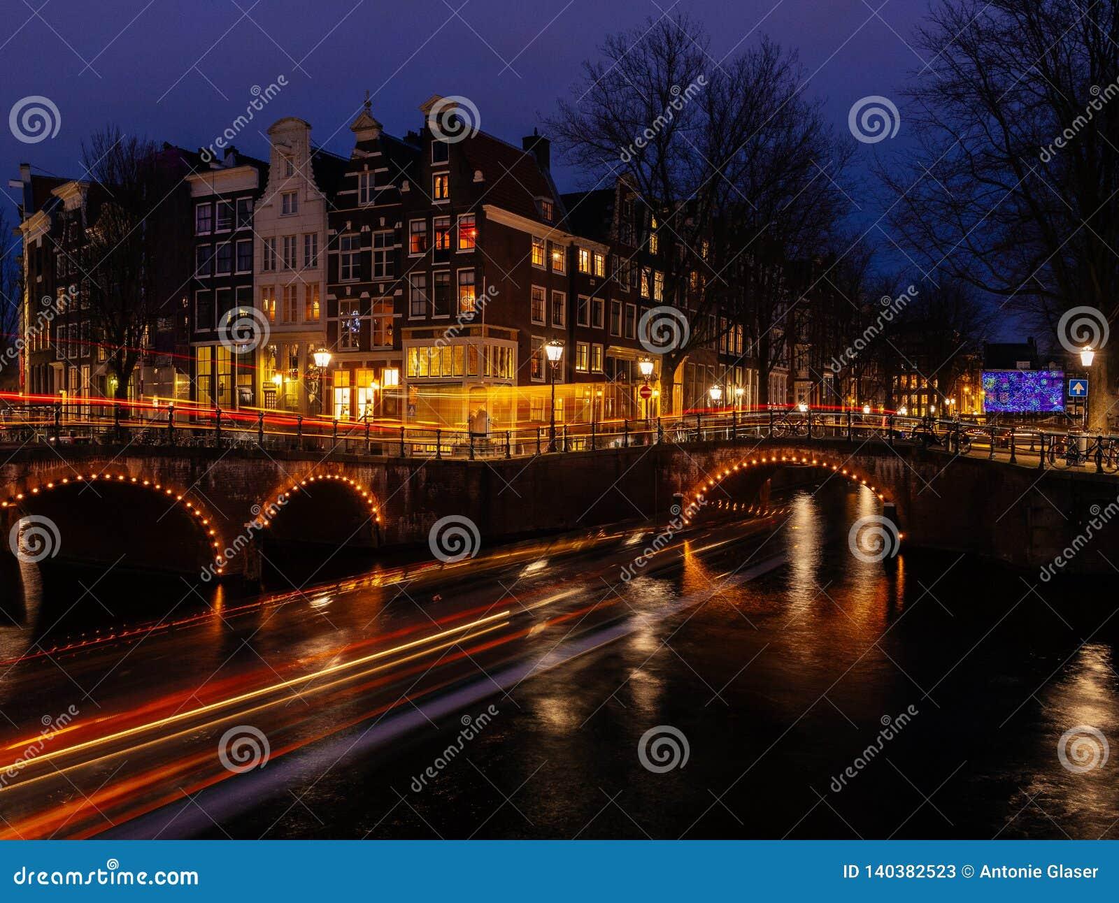 Typische Kanallandschaft Amsterdams nachts mit hellen Spuren und reflektierendem Wasser