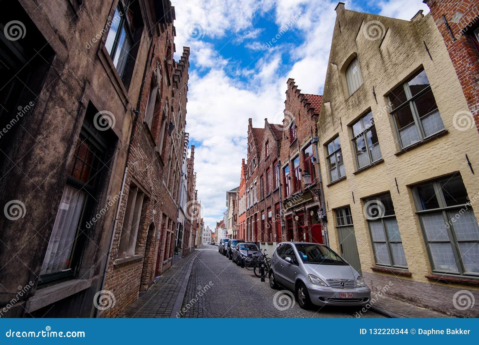 Typisk gammal smal stenlagd gata med traditionella tegelstenhus i Bruges