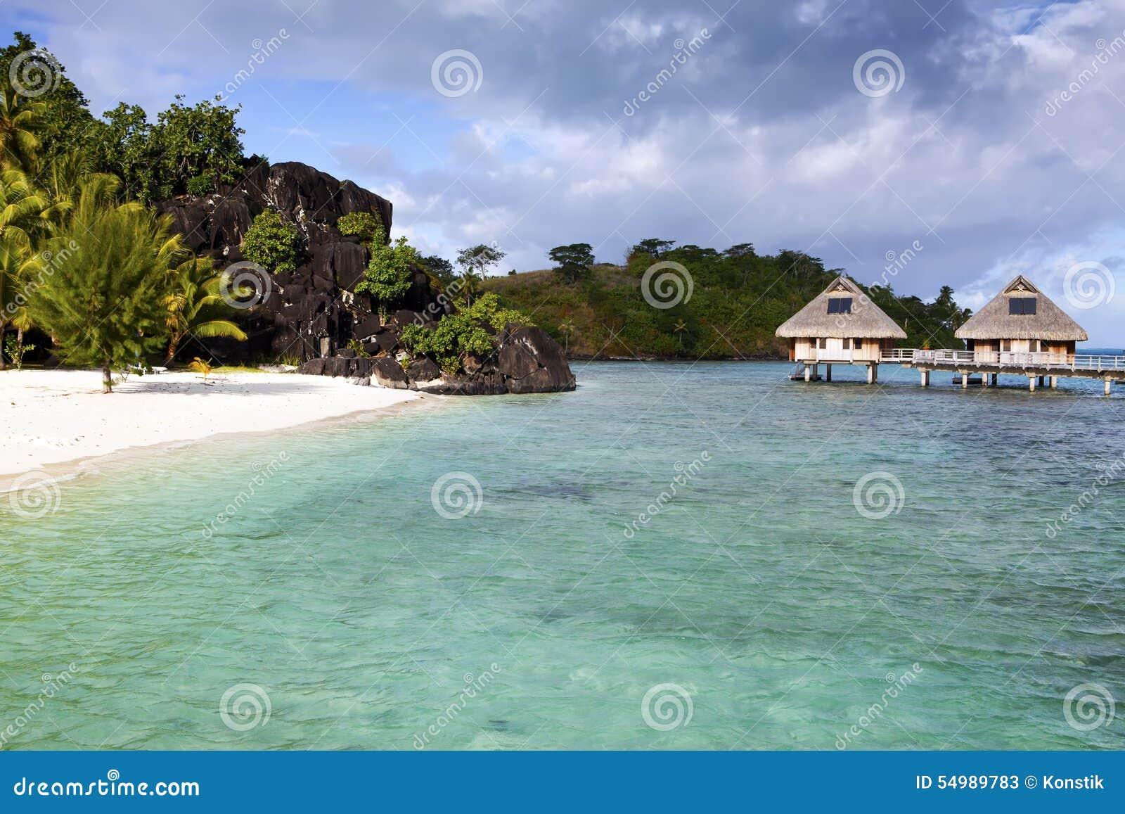 Typisk Polynesian landskap - ö med palmträd och små hus på vatten i havet och bergen på en bakgrund