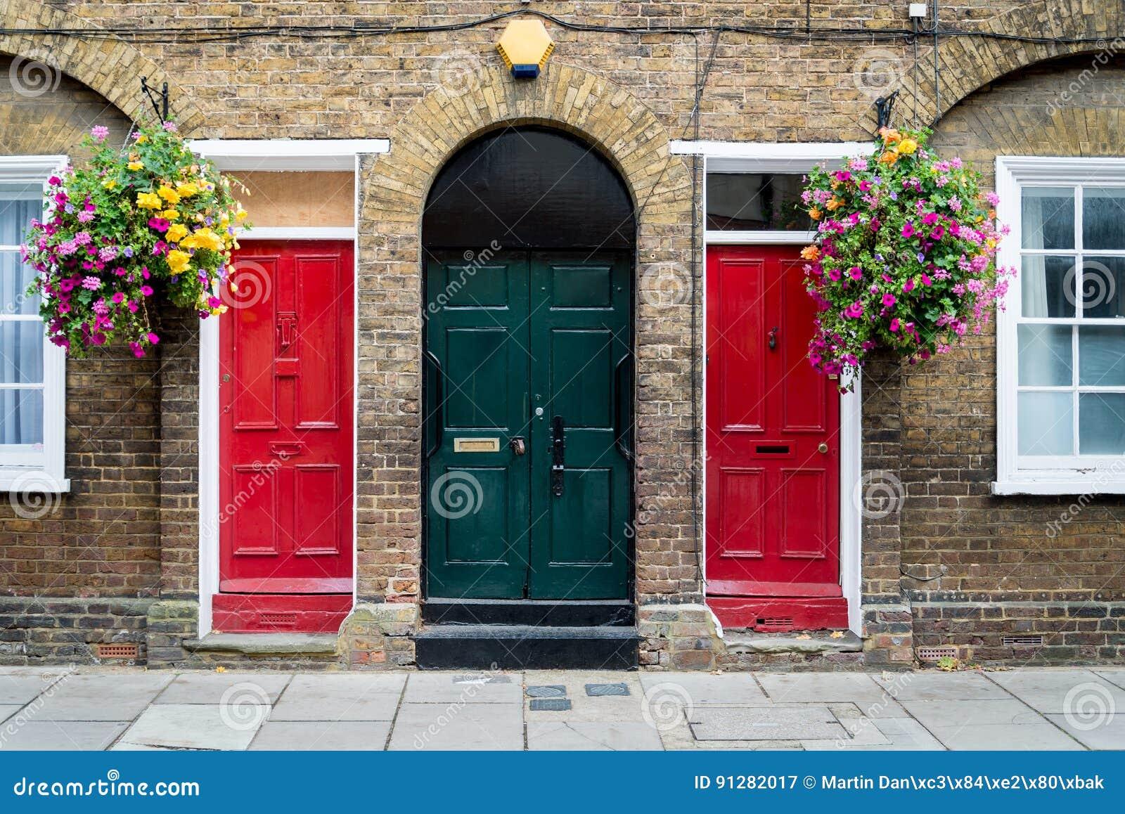 Typiska brittiska dörrar med ringklockan i London Två colorfulldörrar