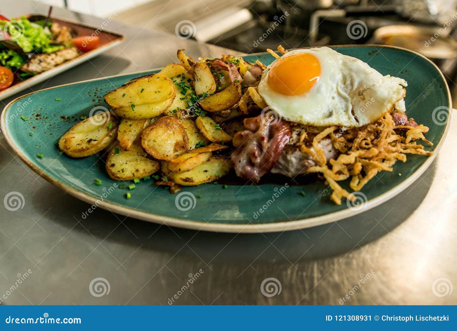 Tyrolean stekte potatisar med köttbacon, champinjoner och ett stekt ägg