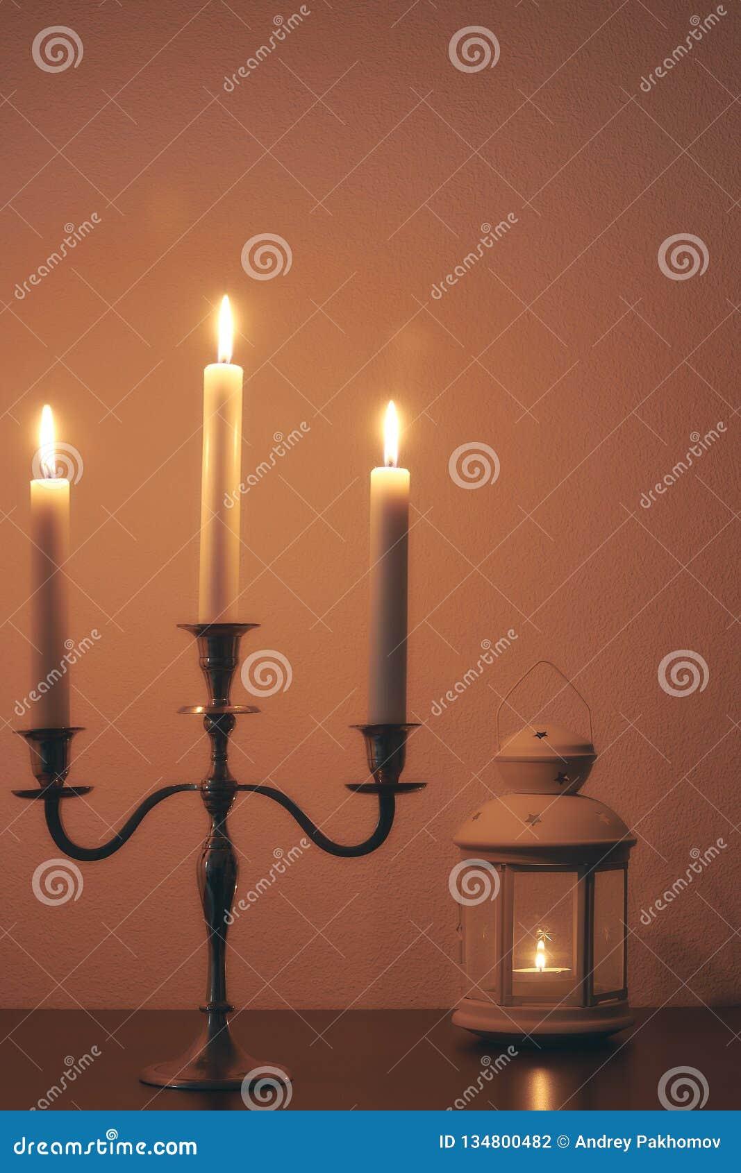 Tyst hem- miljö på natten vid levande ljus Vita stearinljus bränner i mörkret fridsam sammansättning