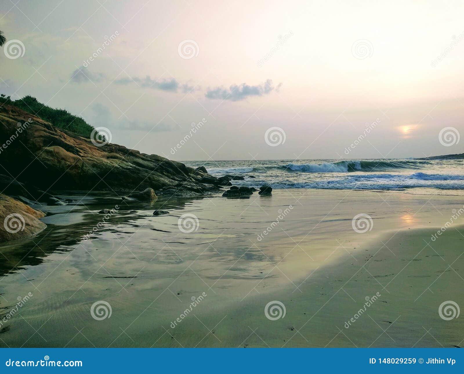 Tysta vågor nära vaggar, sikten från den Kovalam stranden, Kerala Eve& x27; s-strand också som är bekant som den Hawa stranden
