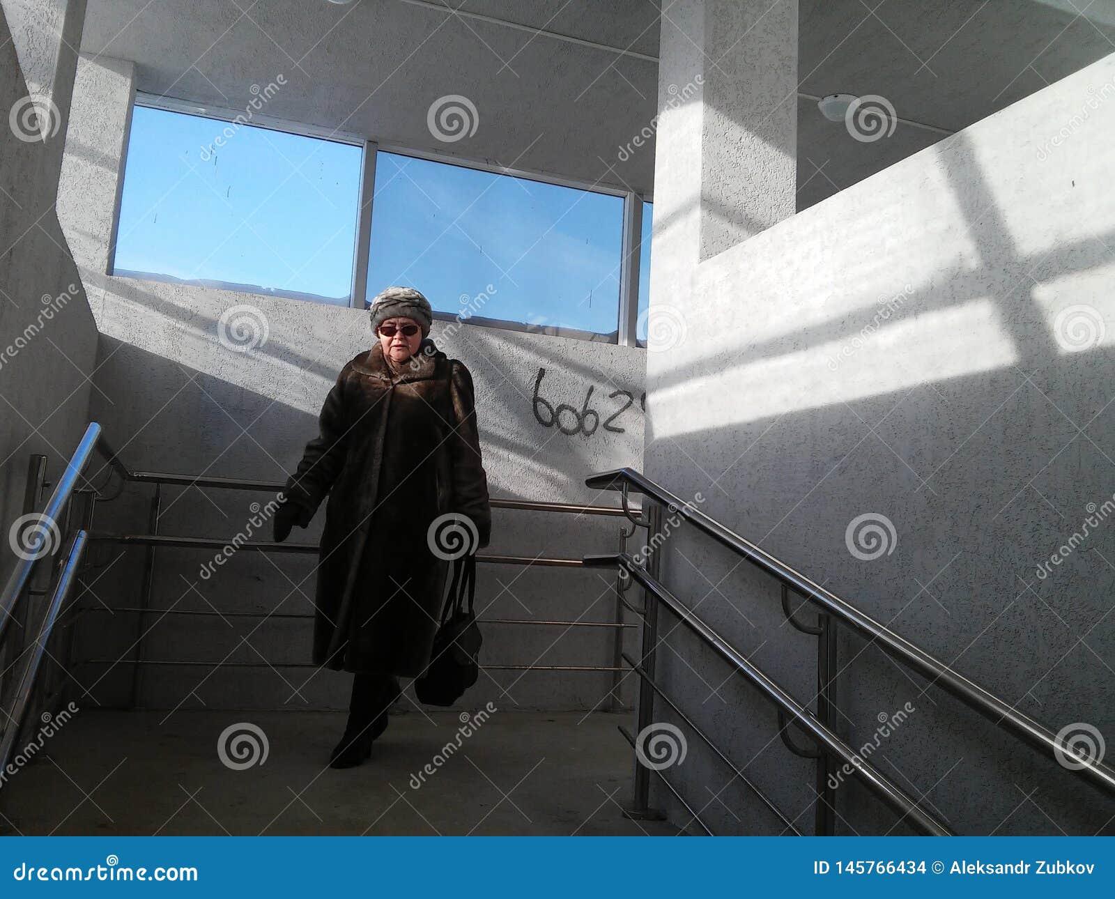 Tyumen, Ρωσία, 11/10/2016 η ηλικιωμένη γυναίκα είναι στην υπόγεια διάβαση