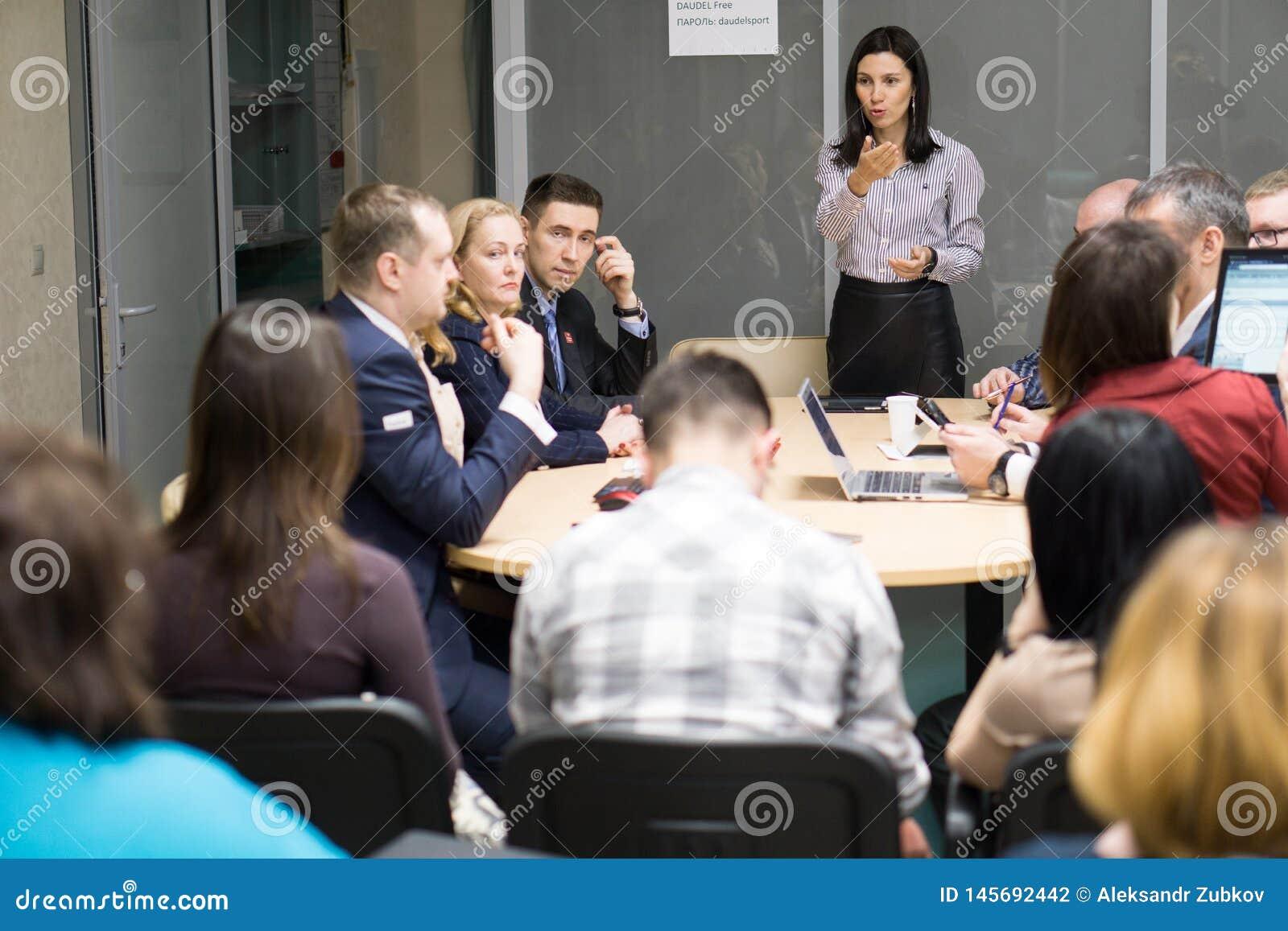 Tyumen, Rosja, 02 21 2017 Żeński kierownik przedstawia raportowego mówienie przy różnorodnego drużynowego hinduskiego pracownika