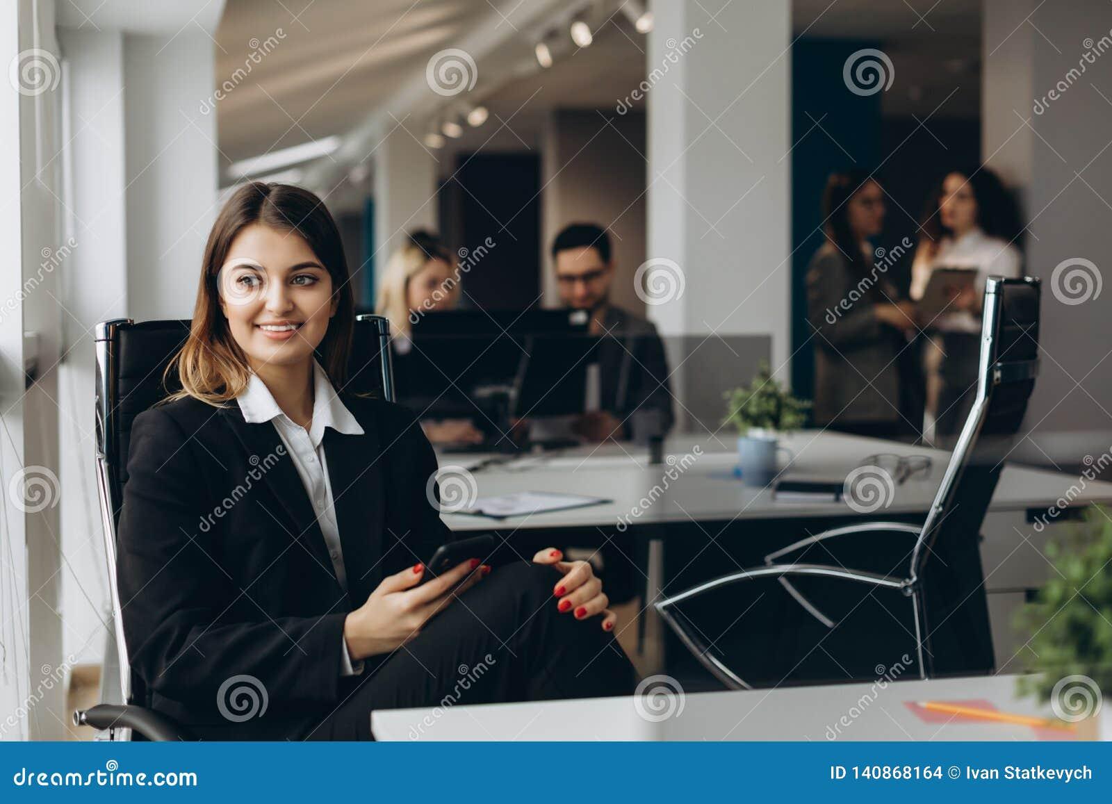 Uśmiechnięta biznesowa kobieta używa telefon komórkowego z kolegami na tle w biurze