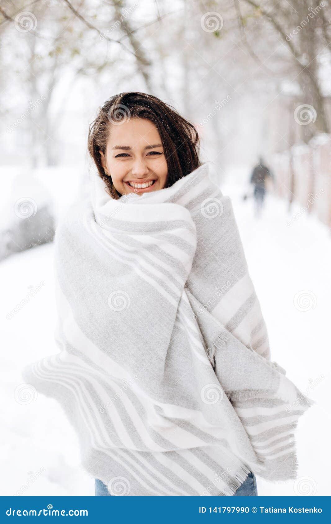 Uśmiechnięta ciemnowłosa dziewczyna zawijająca w szarym szaliku stoi w śnieżnej ulicie na zima dniu