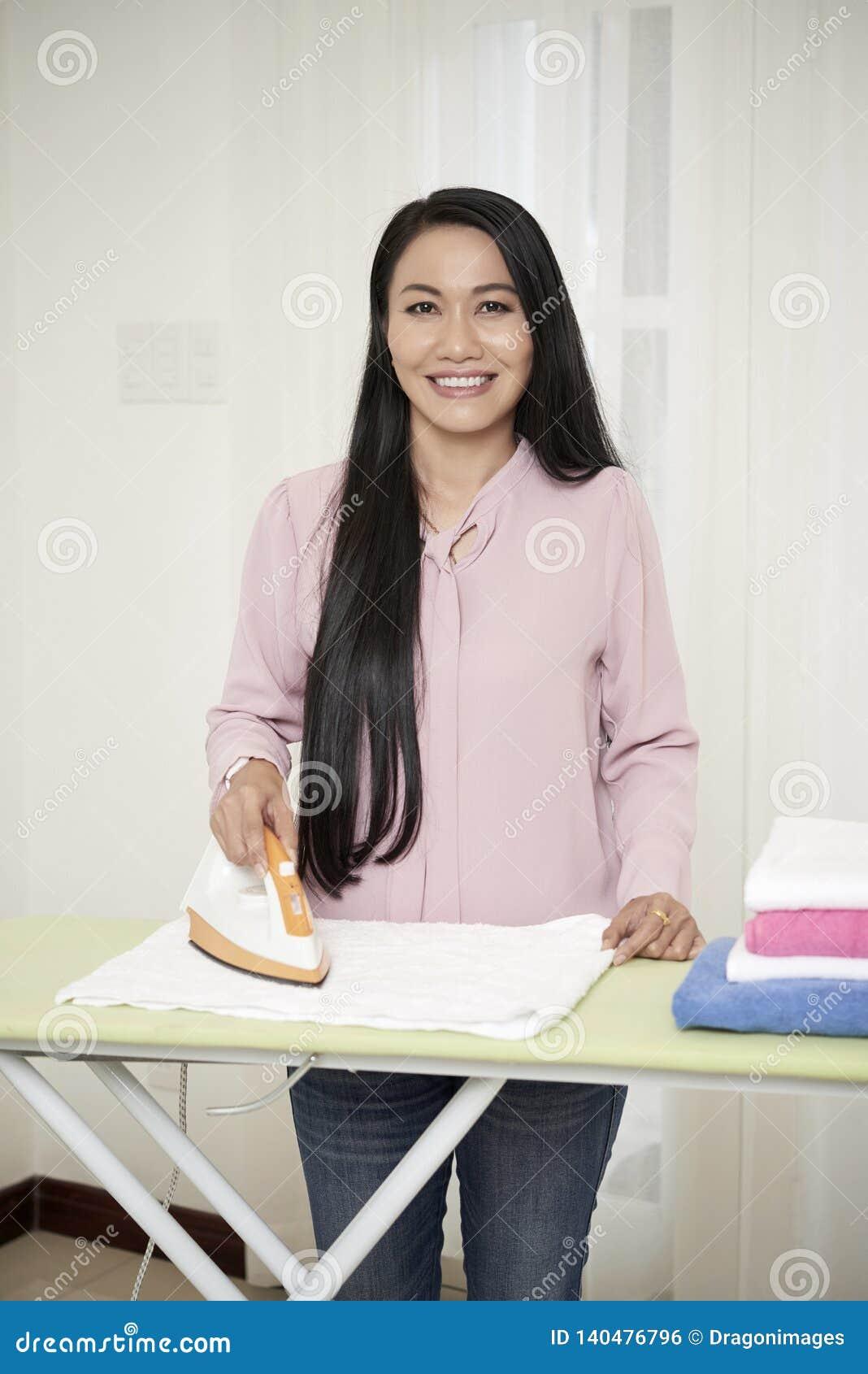 Uśmiechnięta dorosła gospodyni domowa z żelazem w domu