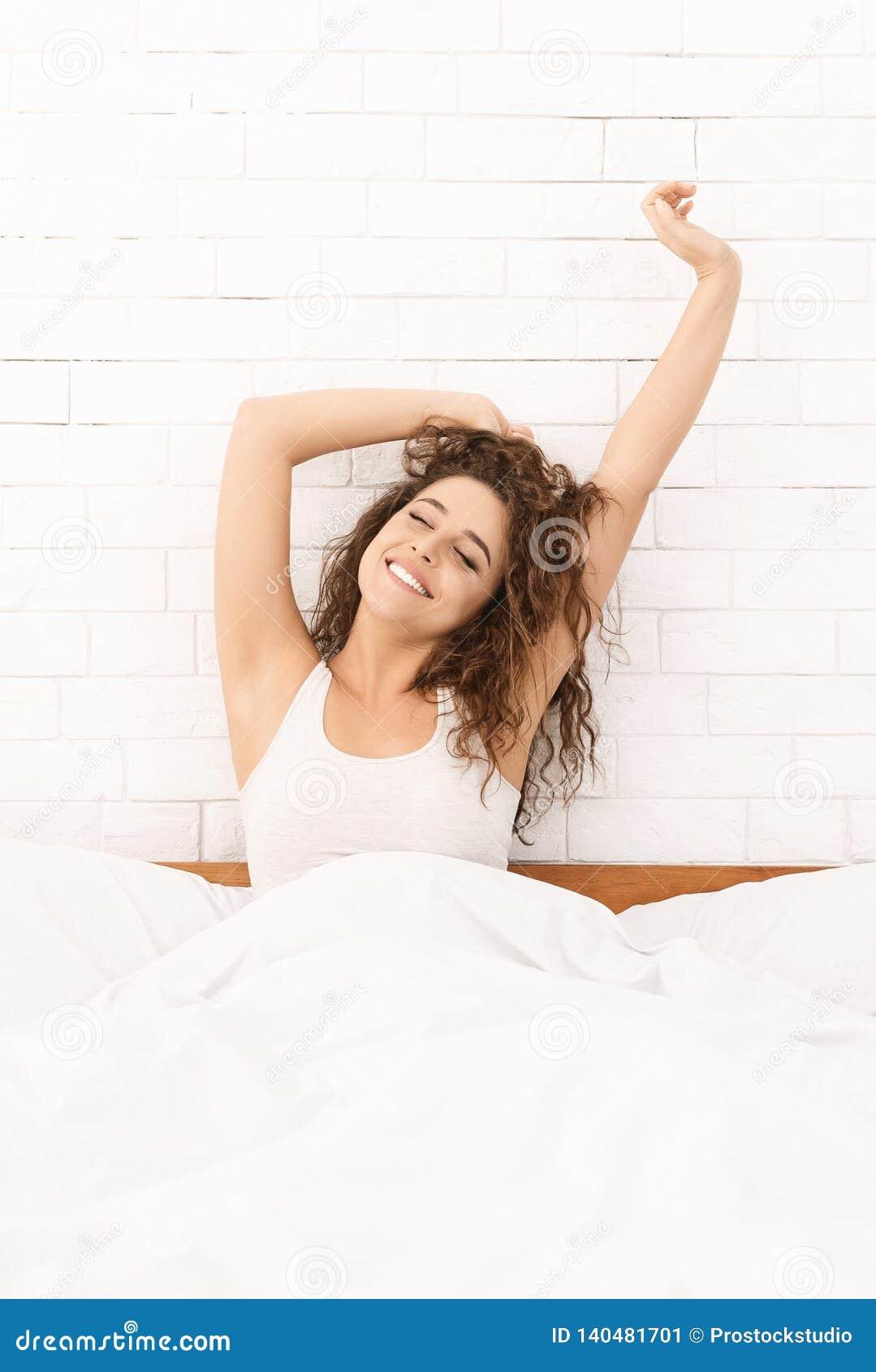 Uśmiechnięta kobieta budzi się w jej łóżku