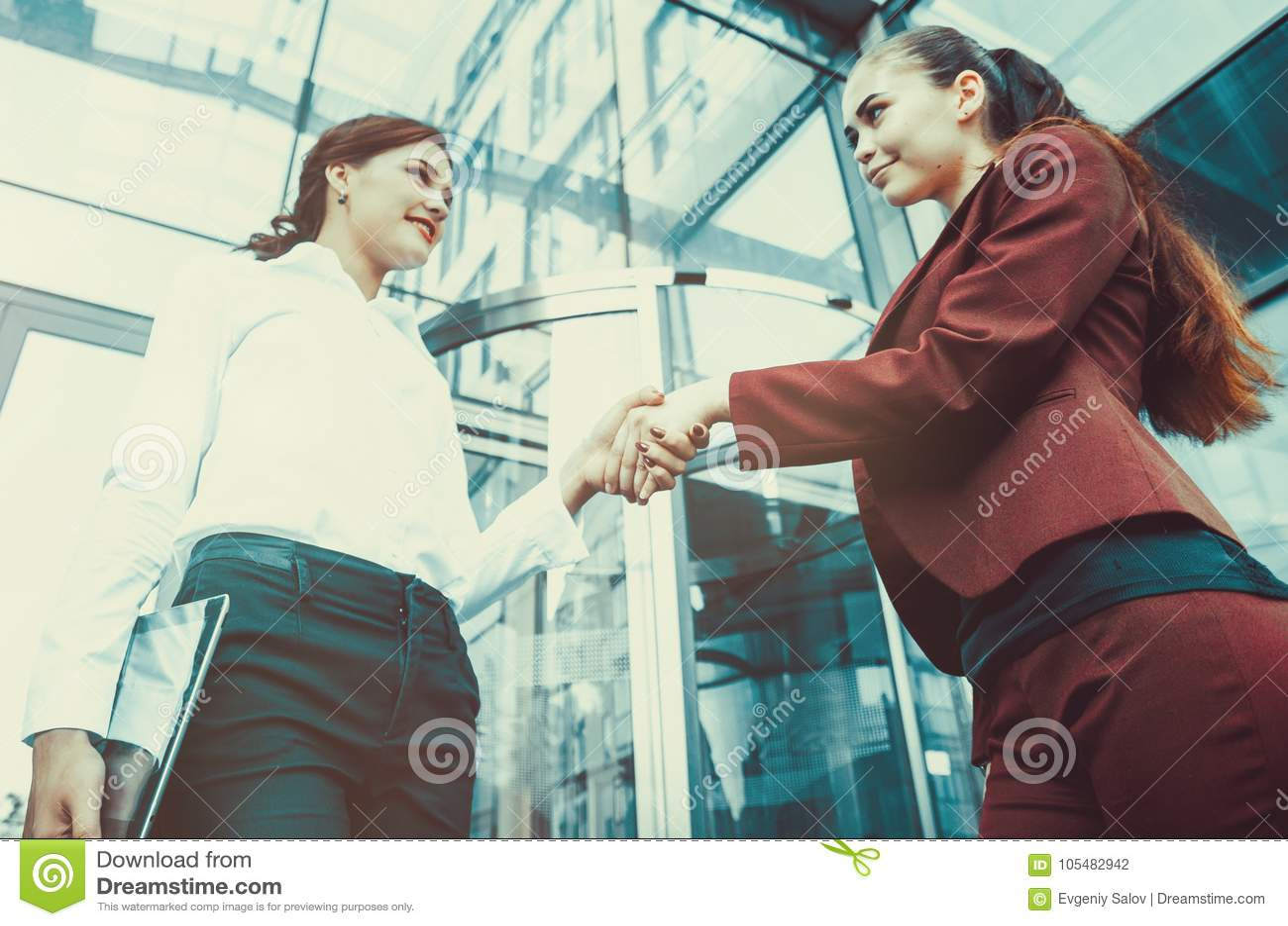 Uścisk dłoni dwa młodej dziewczyny przeciw tłu wielo-