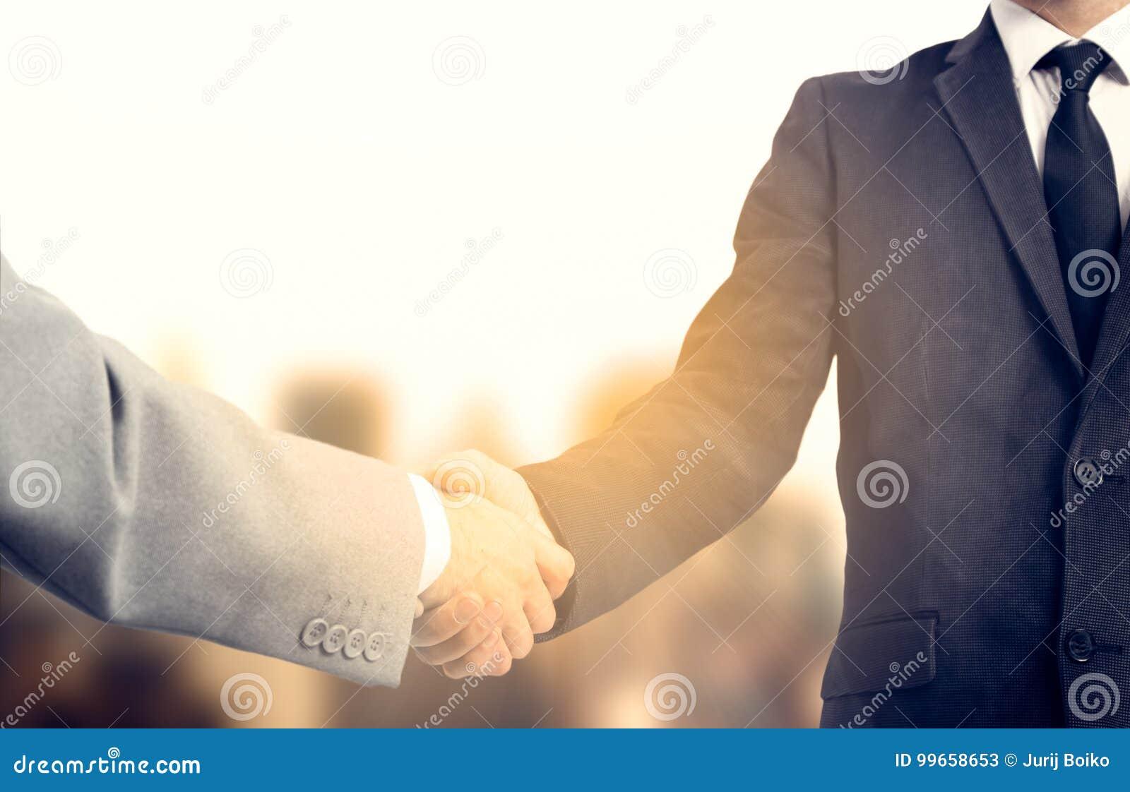 Uścisk dłoni i ludzie biznesu pojęć Dwa mężczyzna trząść ręki nad pogodnym sity tłem partnerstwo
