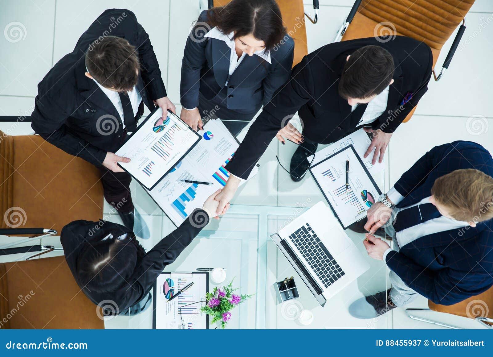 Uścisku dłoni kierownik i Finansowy dyrektor po zatwierdzenia pieniężny plan firma w miejscu pracy