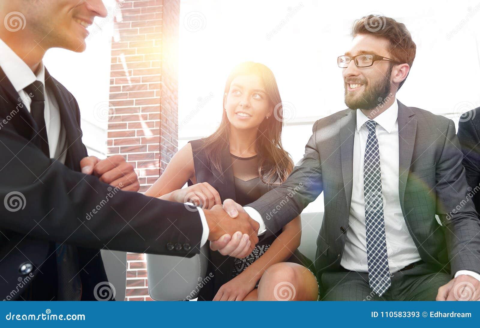 Uścisku dłoni kierownik i klient przy spotkaniem w biurowym lobb