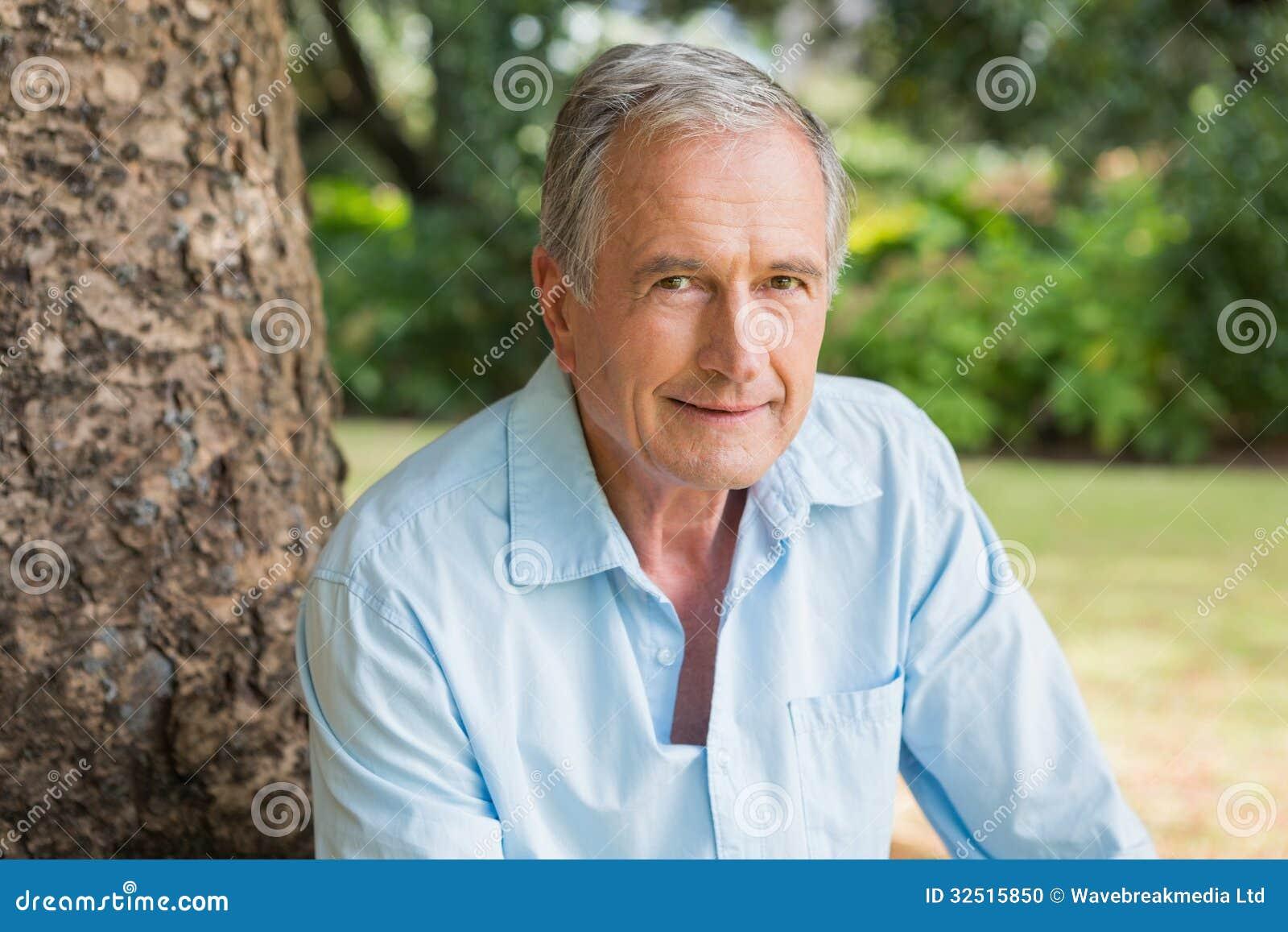 Uśmiechać się przechodzić na emeryturę mężczyzna obsiadanie na drzewnym bagażniku