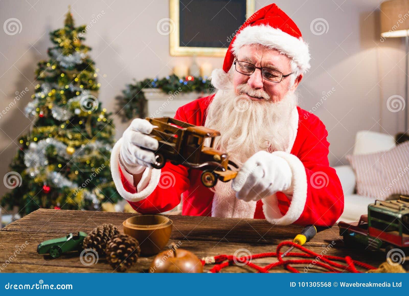Uśmiechać się Santa Claus patrzeje zabawkarskiego samochód w żywym pokoju