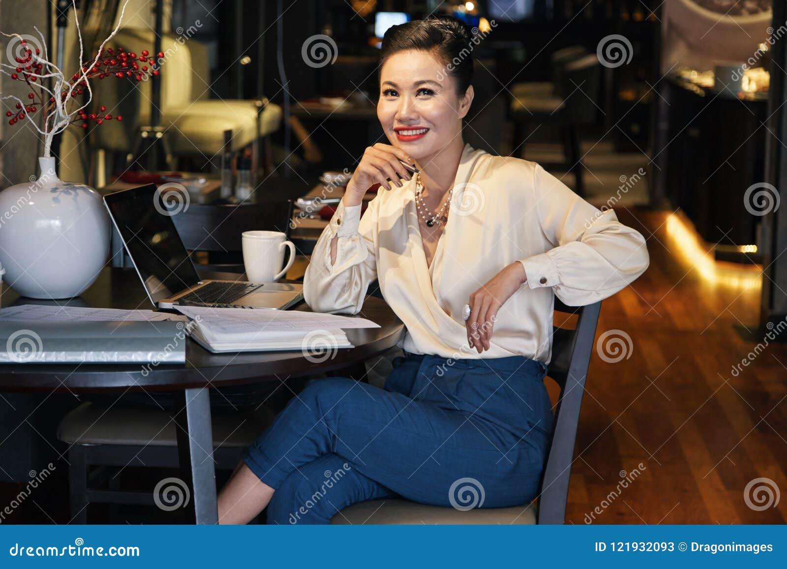 Uśmiechać się zrelaksowanego Azjatyckiego bizneswomanu obsiadanie w kawiarni