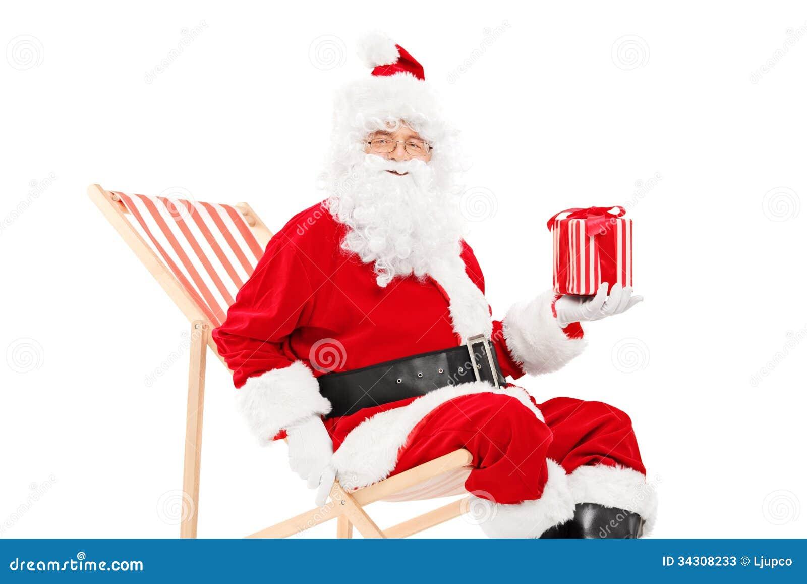 Uśmiechający się Święty Mikołaj obsiadanie na plażowym krześle mieniu i prezent