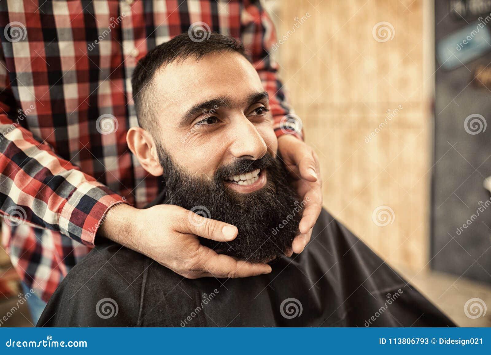 Uśmiechający się zadowolonego modnisia klienta odwiedza fryzjera męskiego sklep, patrzeje g