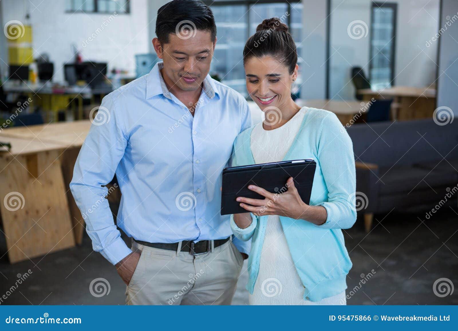 Uśmiechnięci biznesowi koledzy dyskutuje nad cyfrową pastylką