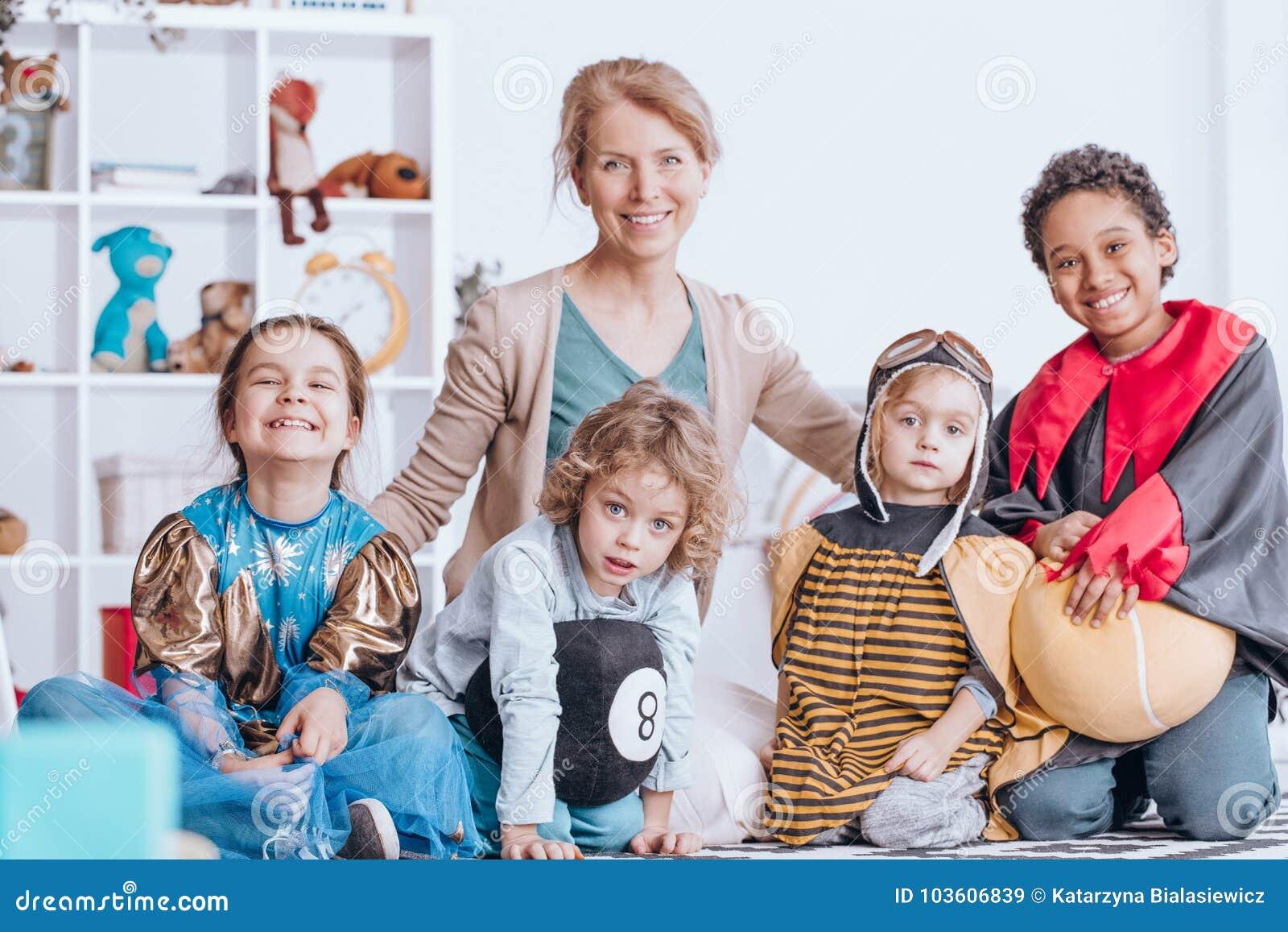 Uśmiechnięci dzieci i nauczyciel