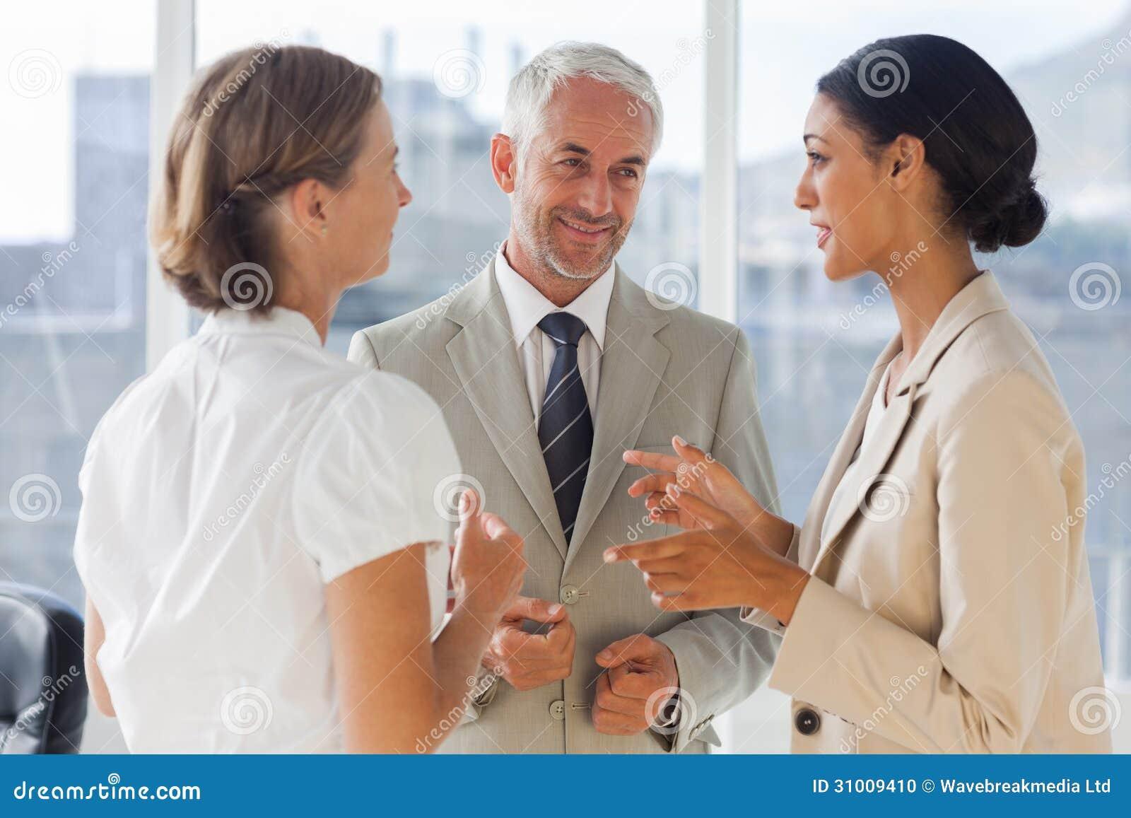 Uśmiechnięci koledzy dyskutuje wpólnie