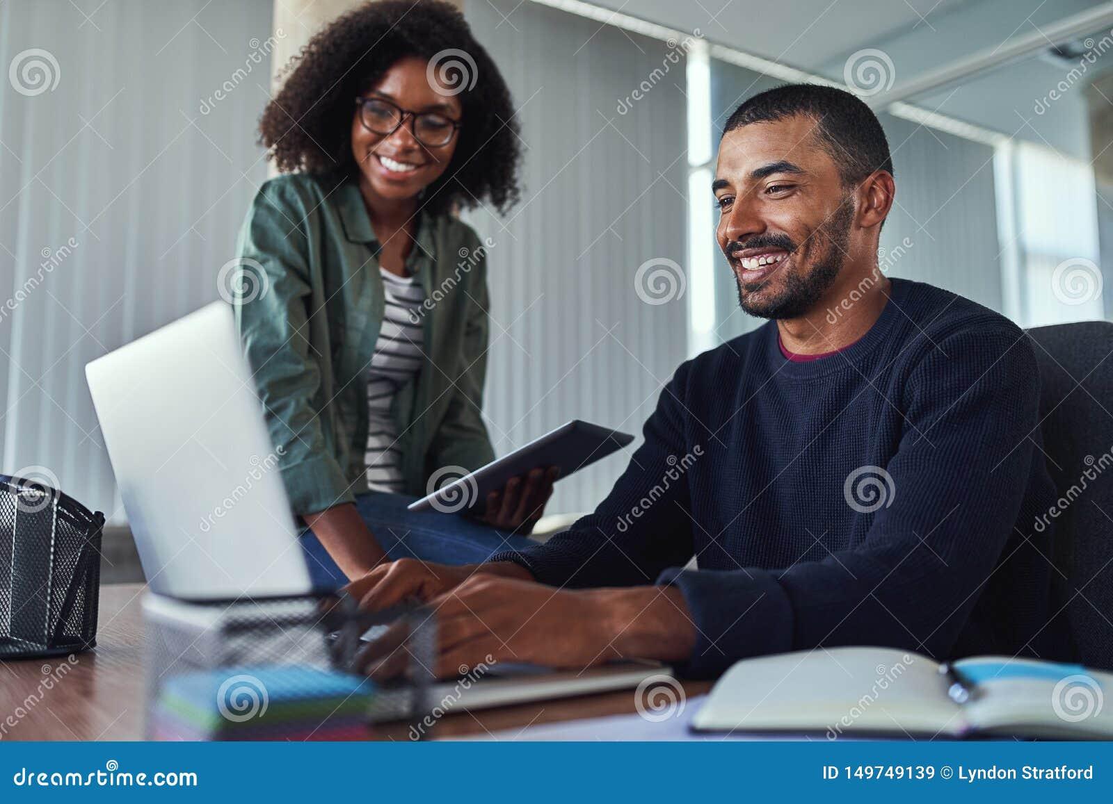 Uśmiechnięci kreatywnie koledzy pracuje wpólnie w biurze