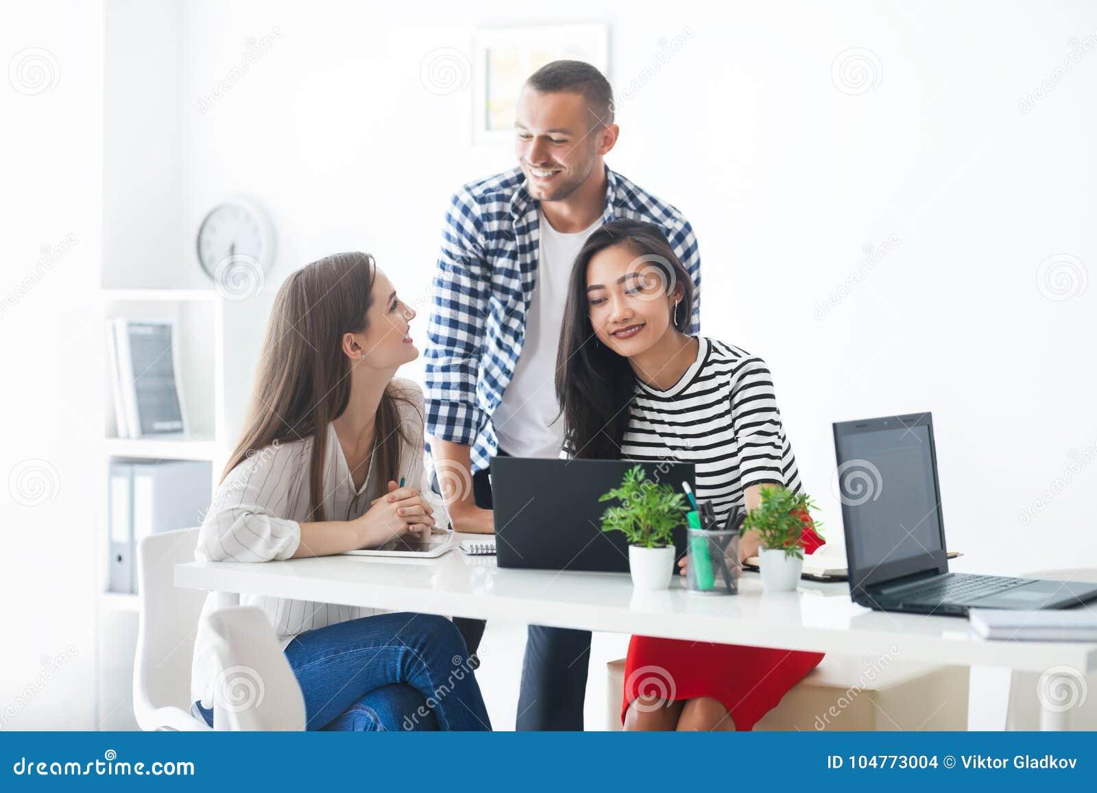 Uśmiechnięci ludzie biznesu dzieli ich pomysły w nowożytnym biurze