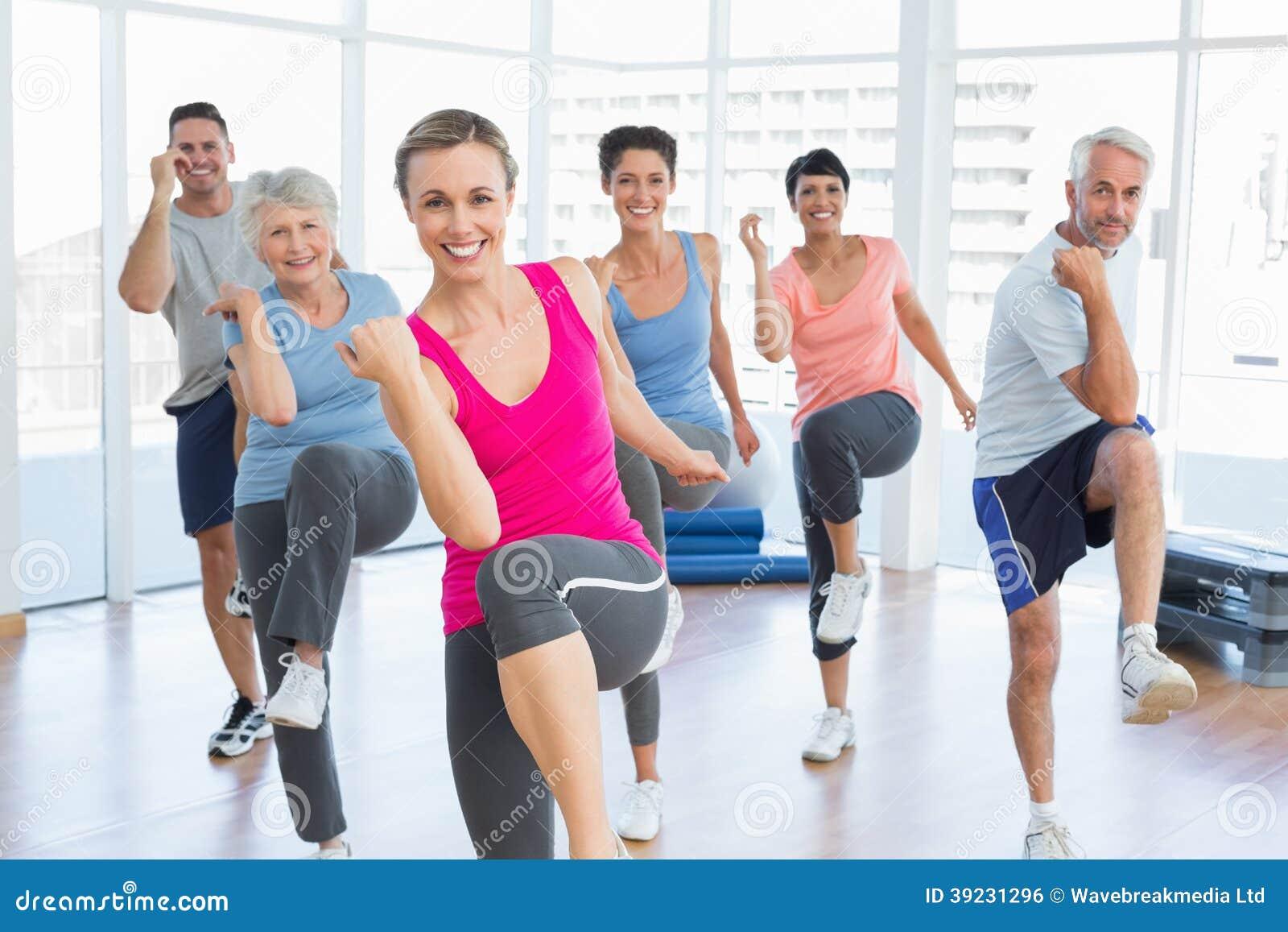 Uśmiechnięci ludzie robi władzy sprawności fizycznej ćwiczeniu przy joga klasą