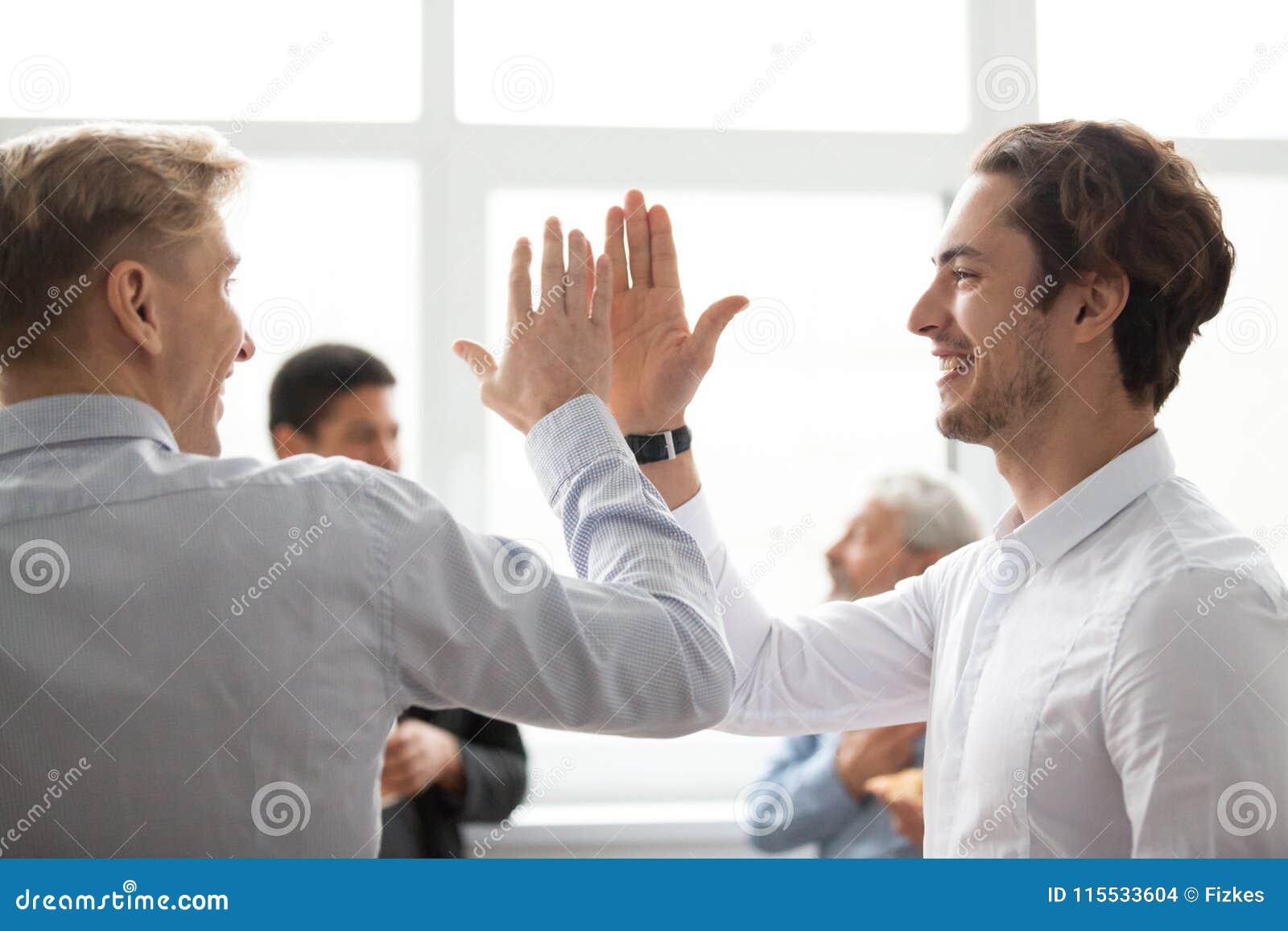Uśmiechnięci męscy koledzy daje wysokości pięć w biurowym świętuje v