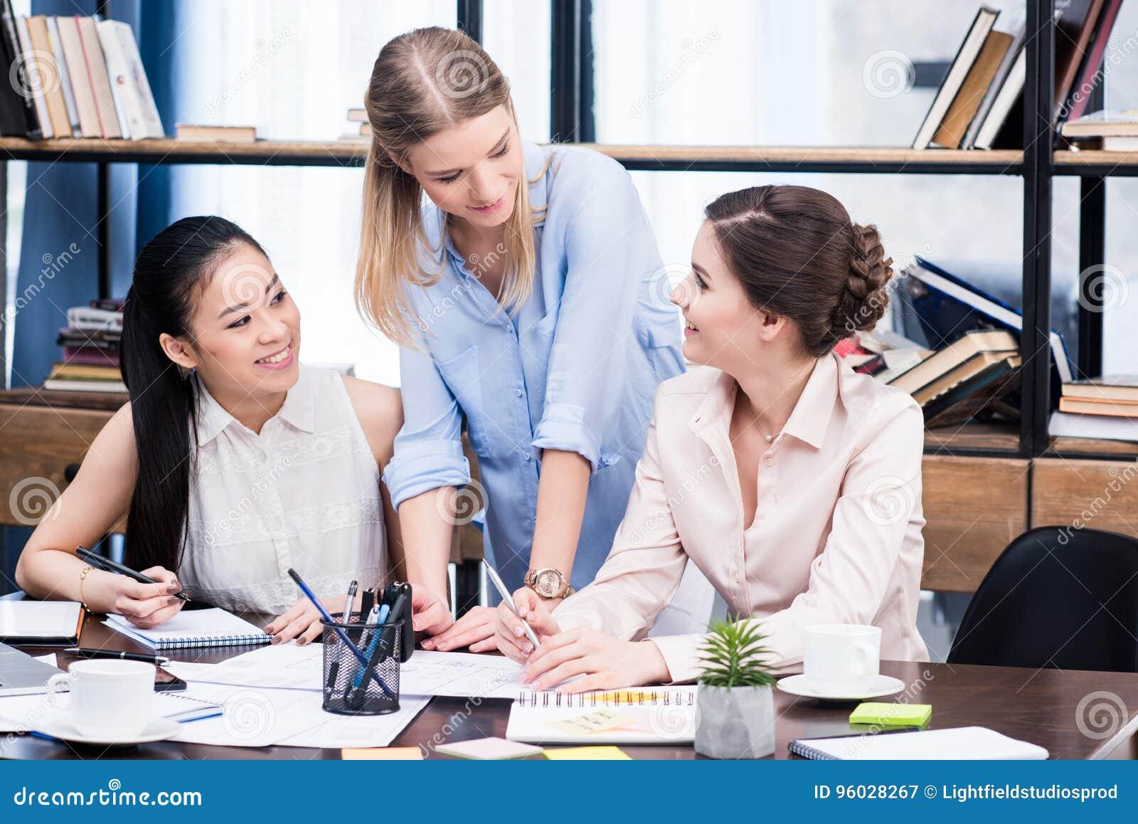Uśmiechnięci młodzi bizneswomany pracuje wpólnie przy miejscem pracy