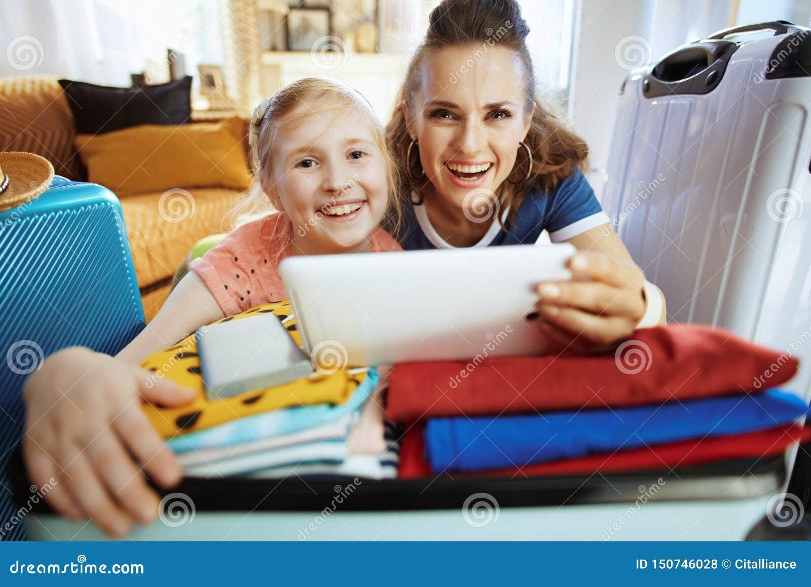 Uśmiechnięci matki i córki turyści kupuje loty online