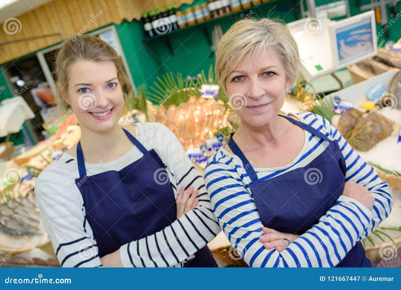 Uśmiechnięci sprzedaż asystenci pracuje przy kontuarem w rybim sklepie