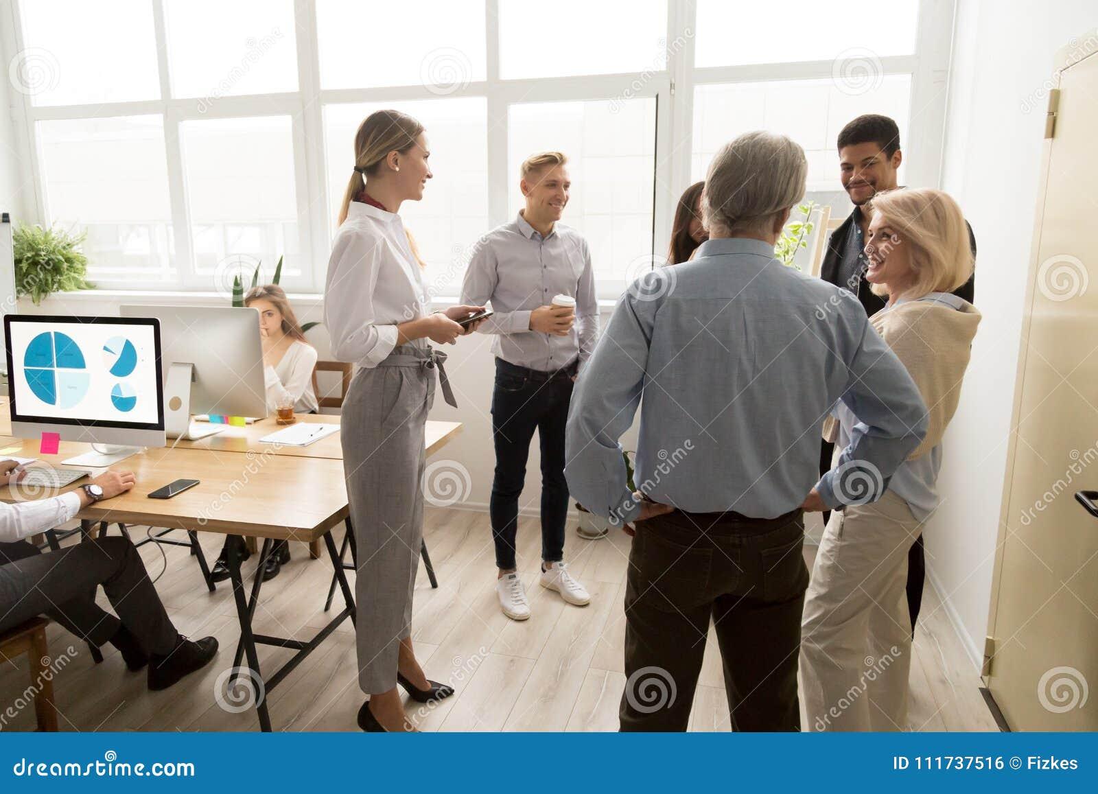 Uśmiechnięci szczęśliwi młodzi i starsi urzędnicy opowiada w coworki