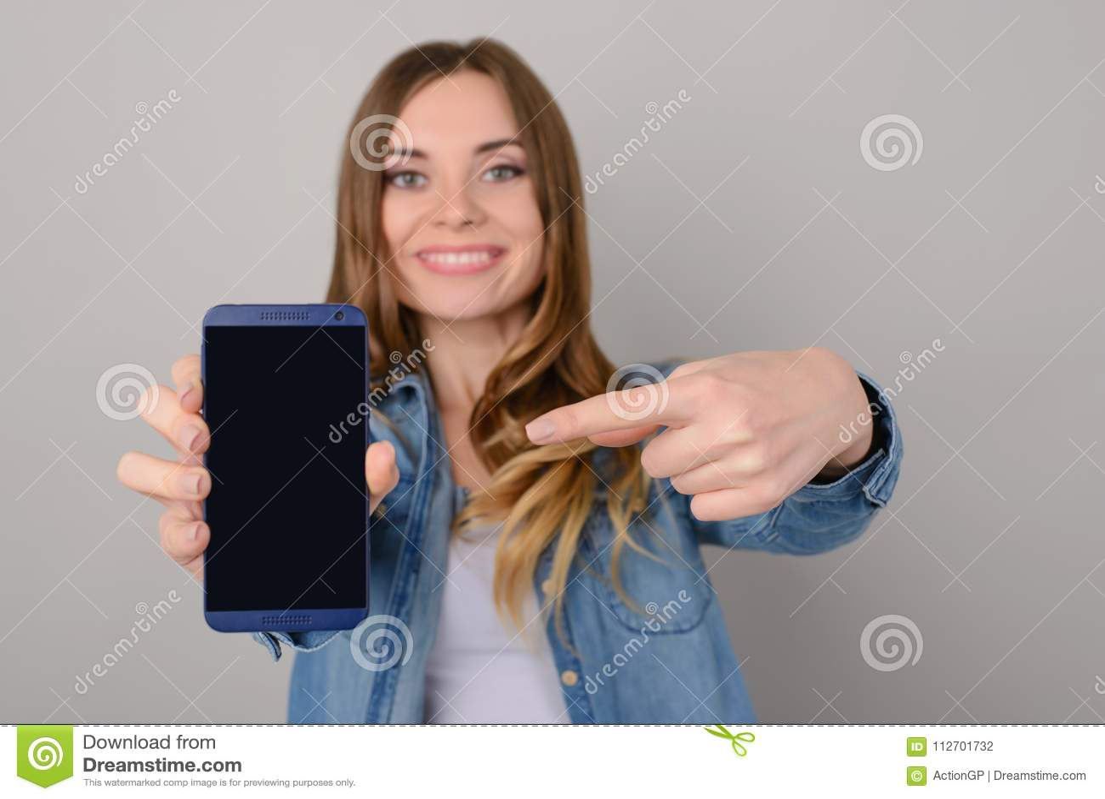 Uśmiechnięta ładna kobieta pokazuje czerni pustego ekran jej smartphone i wskazuje na nim z jej palcem; odizolowywający na popiel