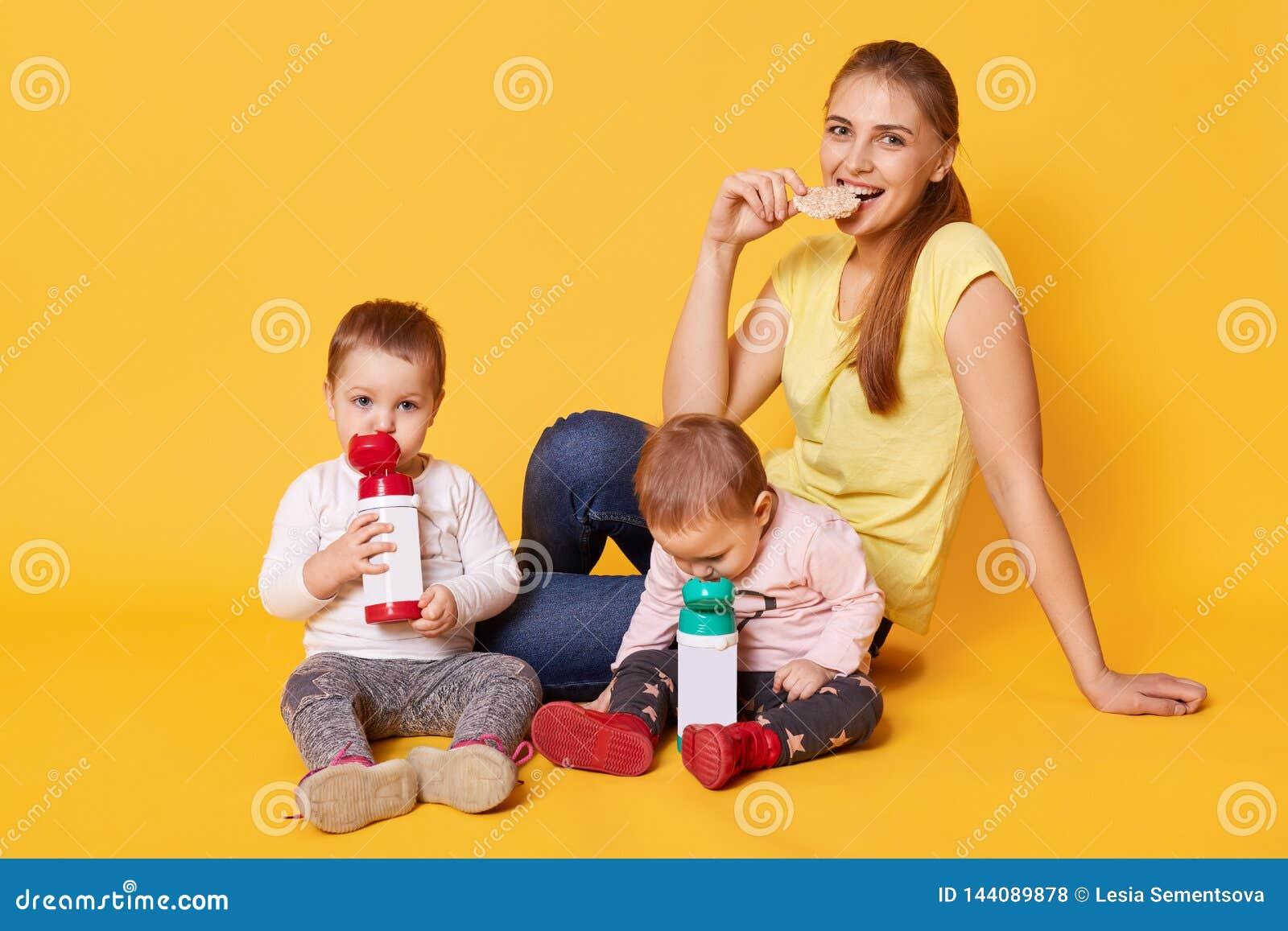 Uśmiechnięta łasowanie matka bierze opiekę jej małe śmieszne córki Spokojni uroczy dzieci piją ciecz i relaksować podczas ich