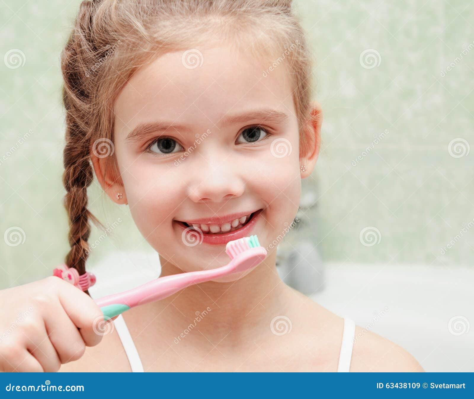 Uśmiechnięta śliczna mała dziewczynka szczotkuje zęby
