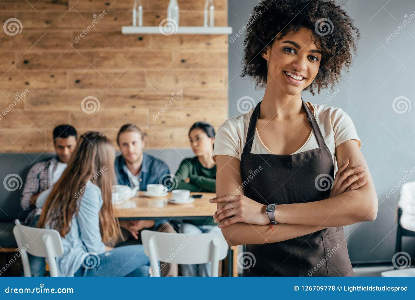 Uśmiechnięta amerykanin afrykańskiego pochodzenia kelnerki pozycja z klientami siedzi behind