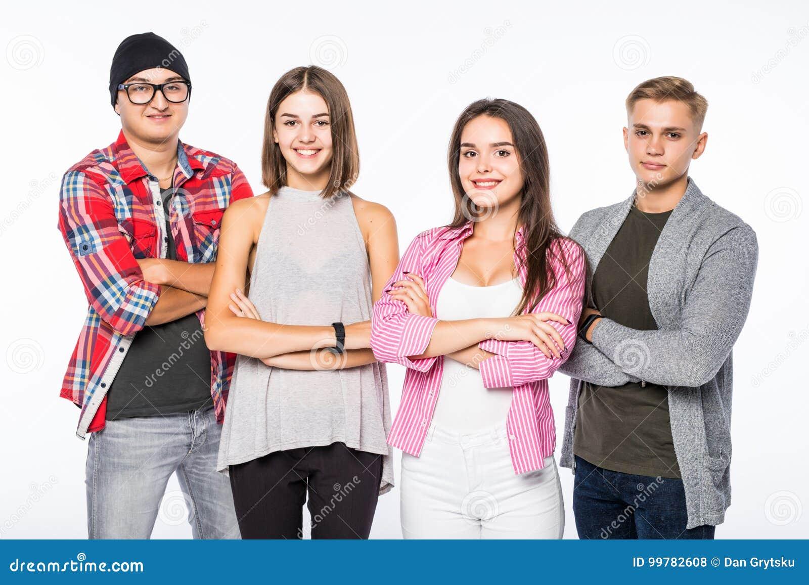 Uśmiechnięta atrakcyjna grupa młodzi ludzie stoi z krzyżować rękami, przeciw białemu tłu