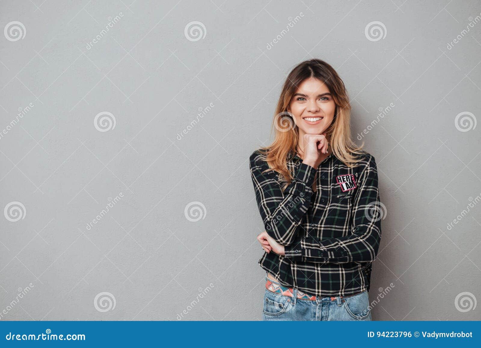 Uśmiechnięta atrakcyjna kobiety pozycja i mienie ręka przy jej podbródkiem