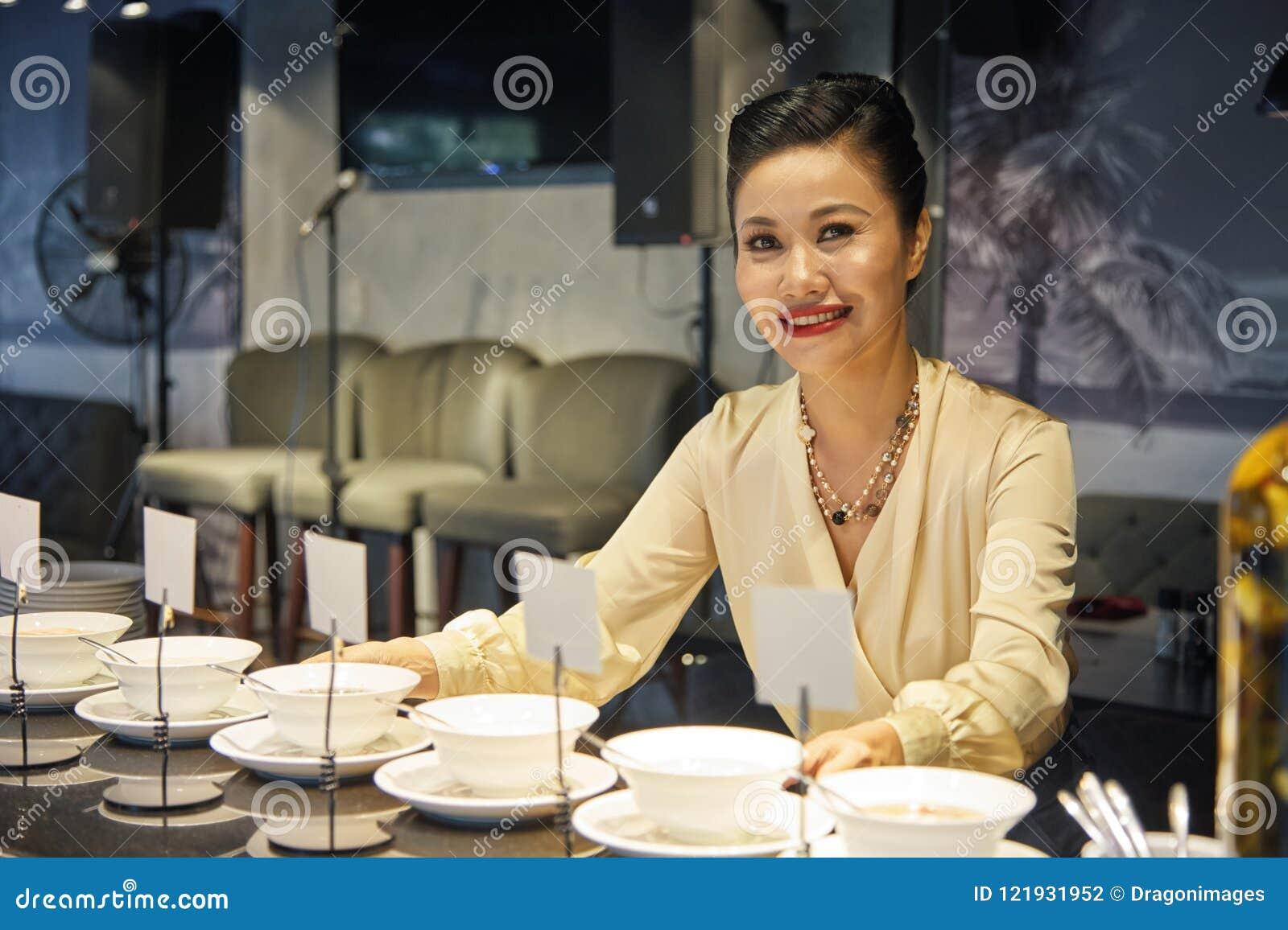 Uśmiechnięta Azjatycka kobieta bierze jedzenie od bufeta