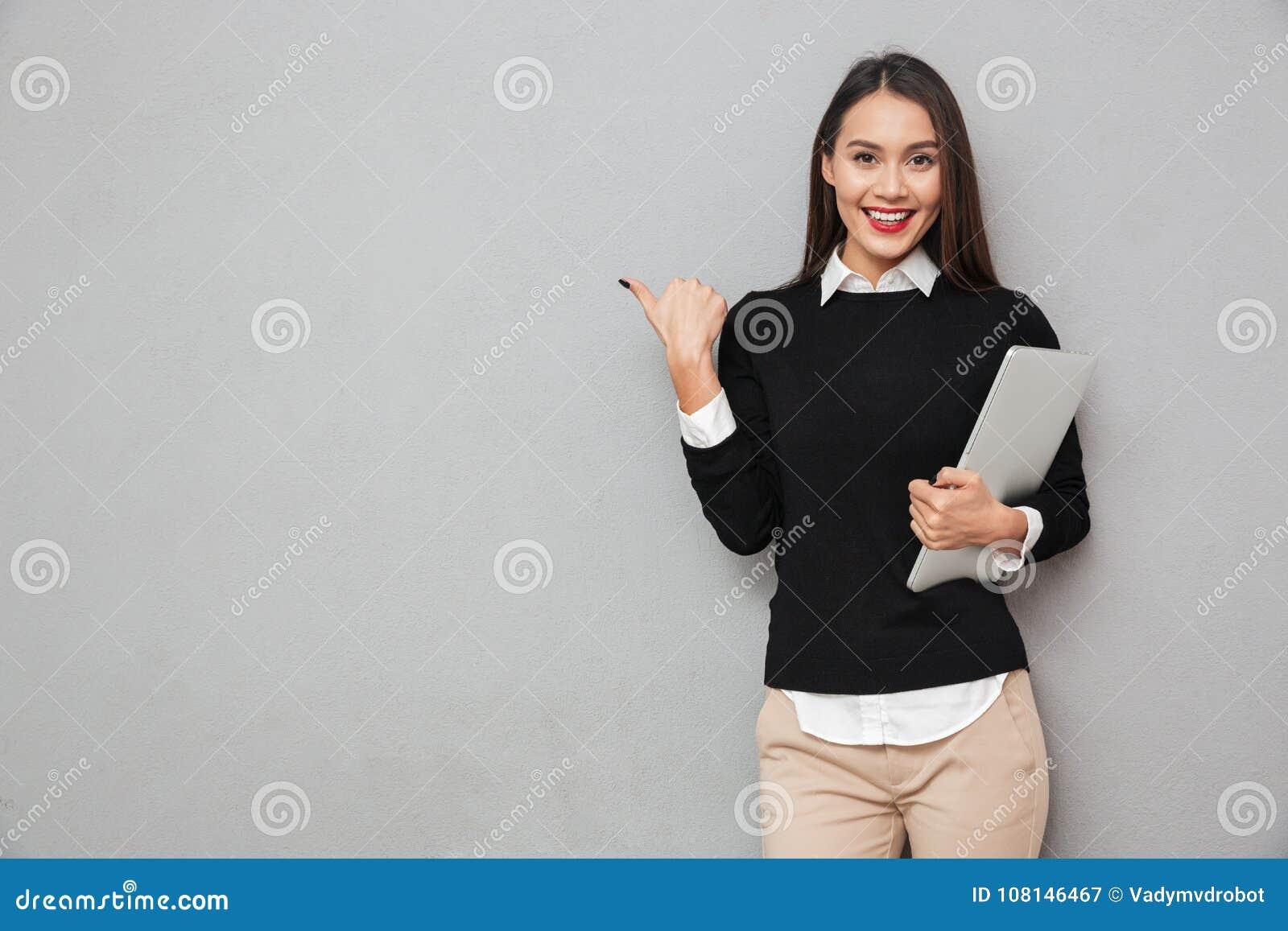 Uśmiechnięta azjatykcia kobieta w biznesu mienia odzieżowym laptopie