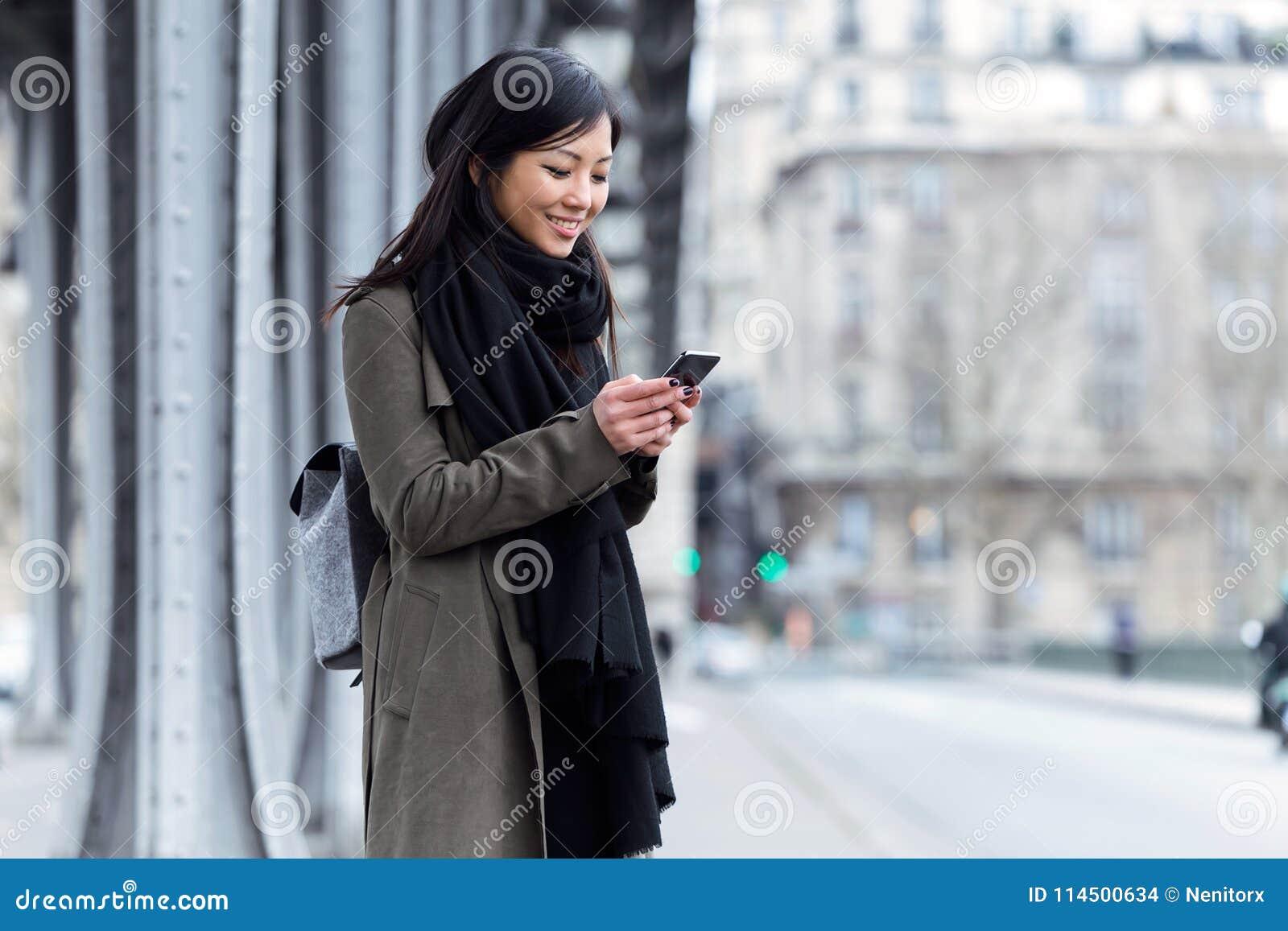 Uśmiechnięta azjatykcia młoda kobieta używa jej telefon komórkowego w ulicie