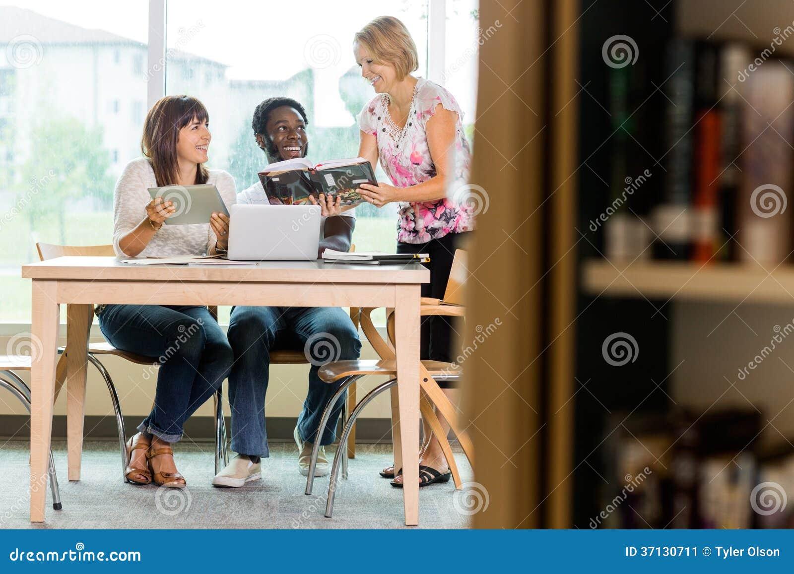 Uśmiechnięta bibliotekarka Pomaga uczni W bibliotece