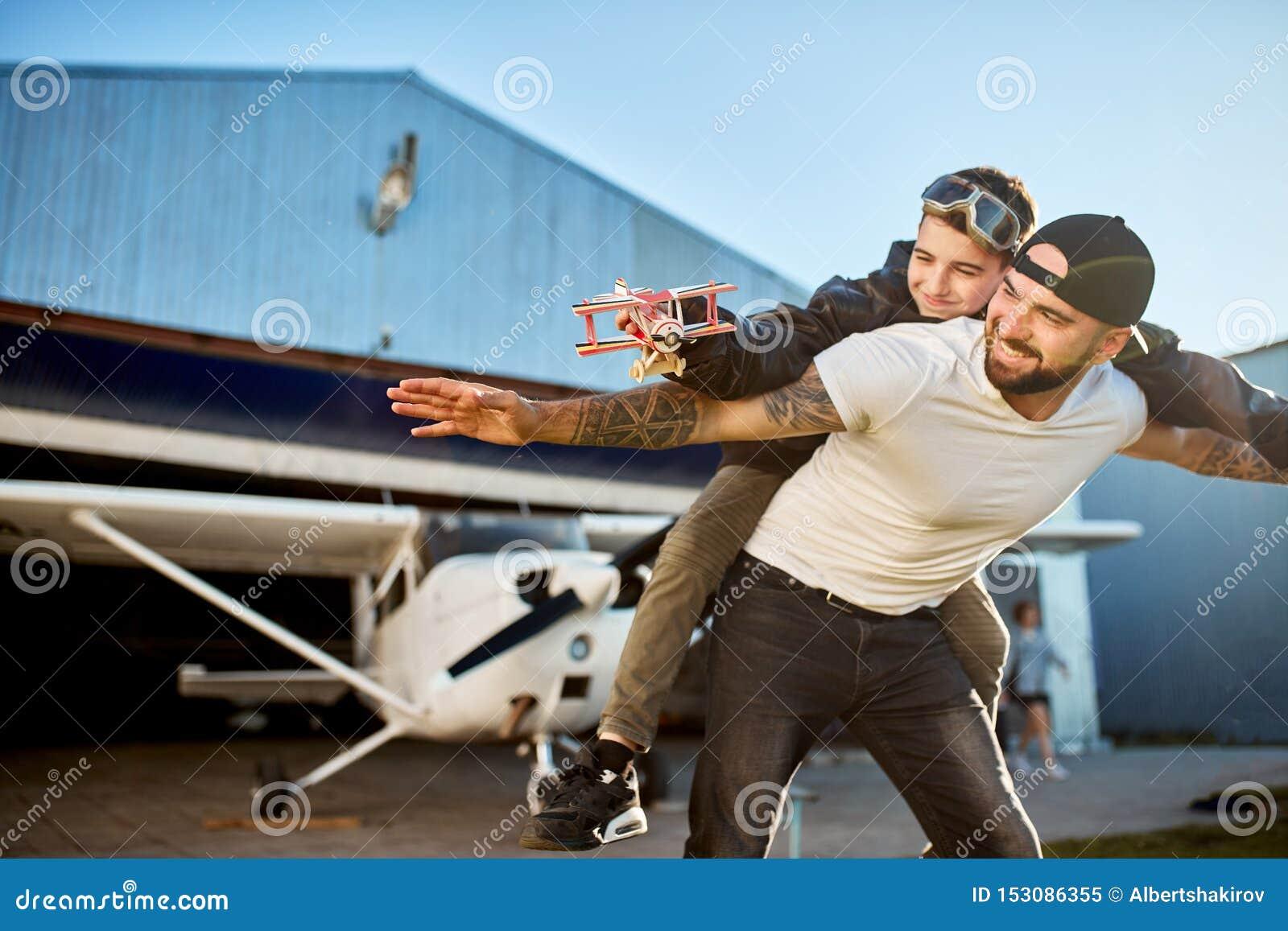 Uśmiechnięta chłopiec z modela samolotem, jadący na ojca plecy, bawić się outside hangar