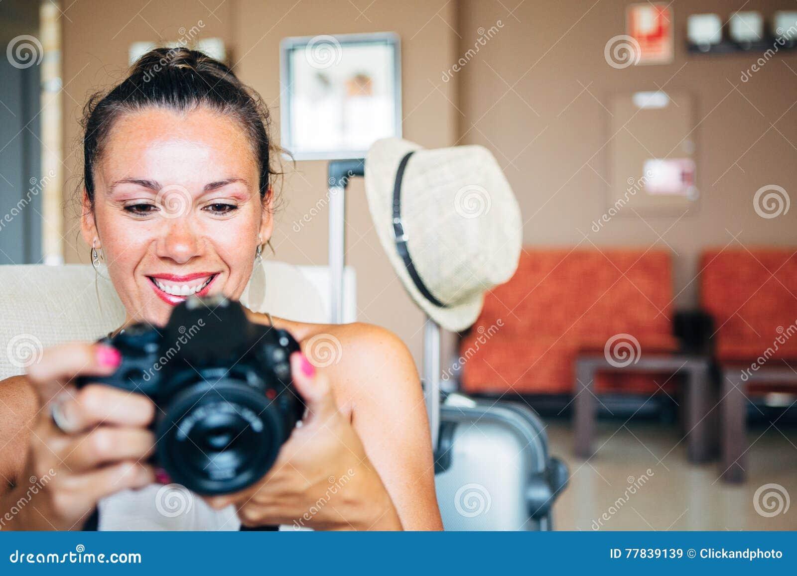 Uśmiechnięta dorosła kobieta patrzeje na kamerze w rękach